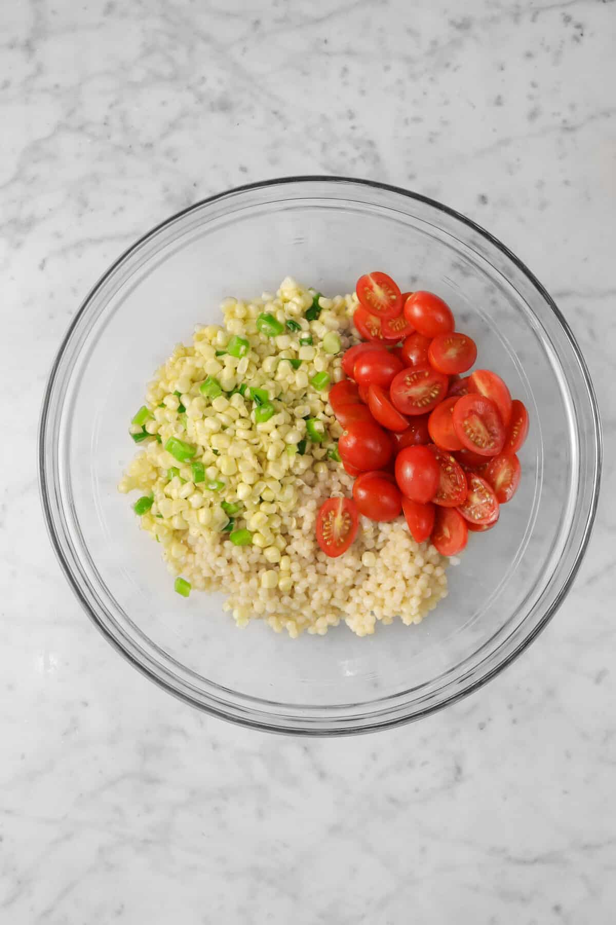 couscous, corn, green onions, and sliced tomatoes in a glass bowl