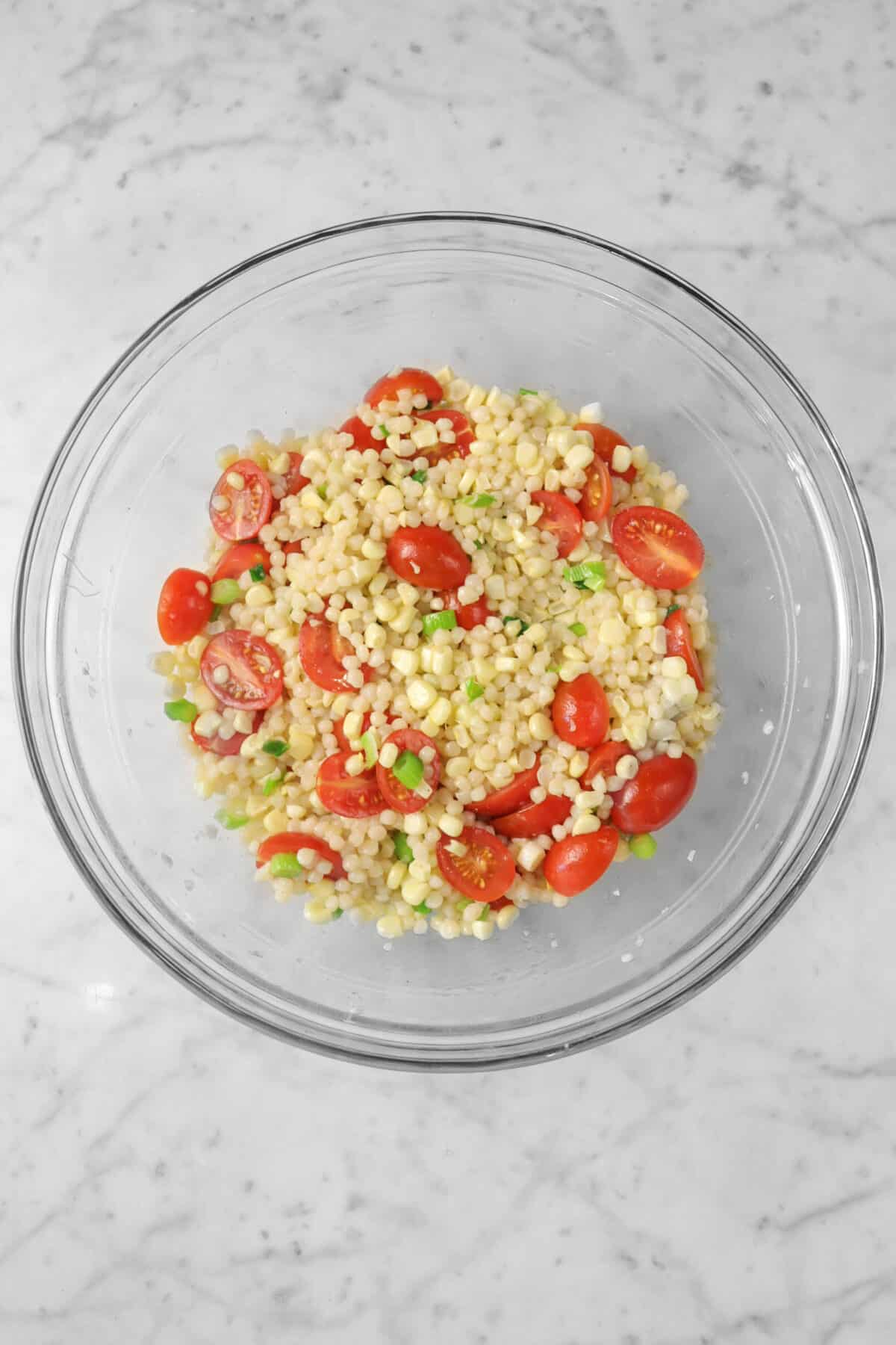couscous corn and tomato salad in a glass bowl