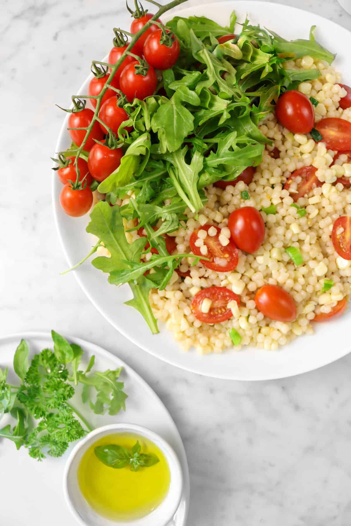 corn and tomato couscous salad with arugula, tomato on the vine, a bowl of oil, and herbs