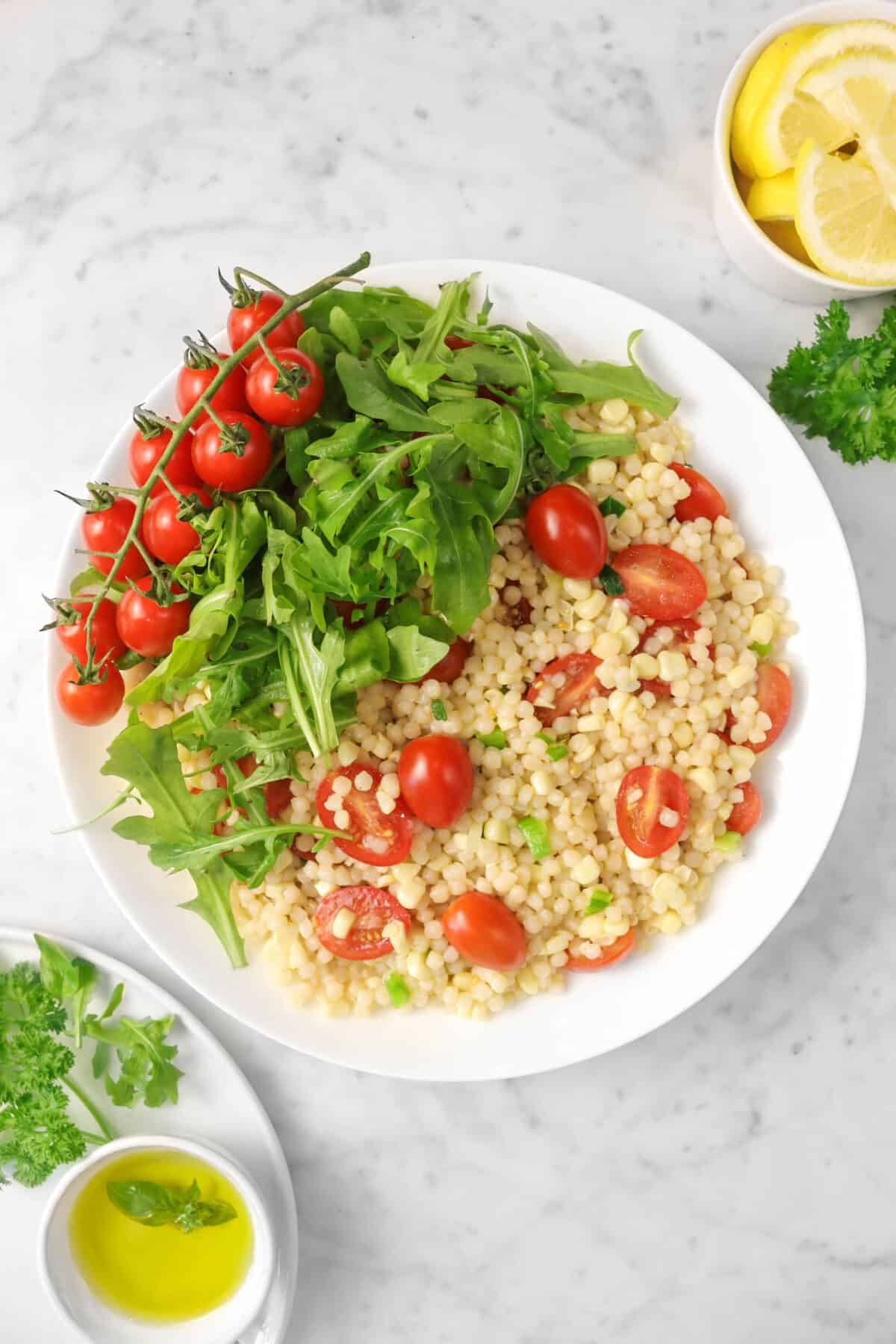 couscous salad in a white bowl with arugula, tomato on the vine, herbs, lemon slices, and oil in a bowl