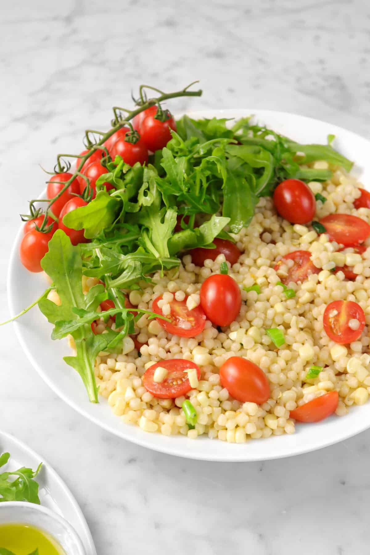 corn and tomato couscous salad with arugula on top and tomatoes on the vine