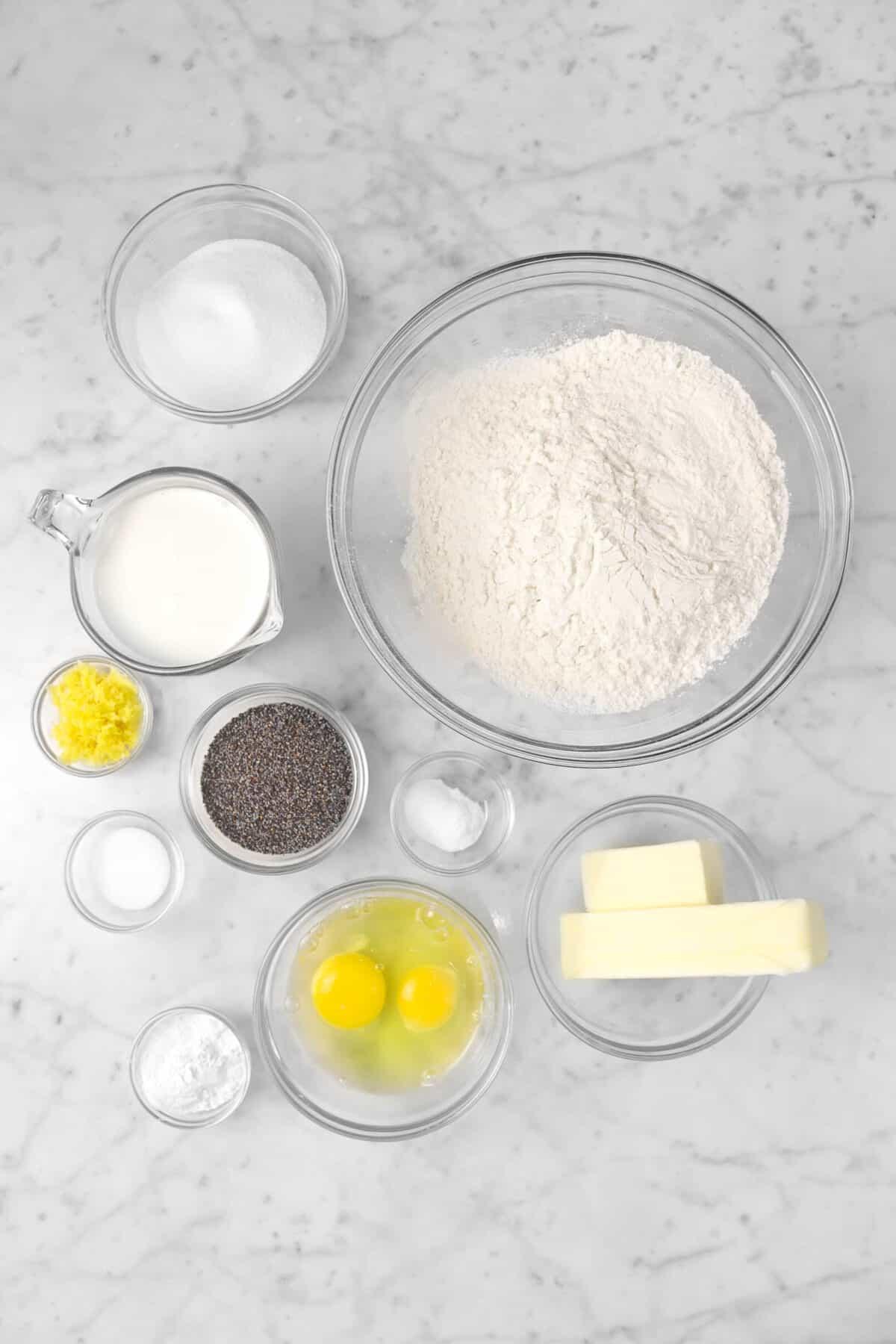 flour, butter, eggs, baking soda, baking powder, poppyseeds, salt, milk, lemon rind, and sugar in glass bowls