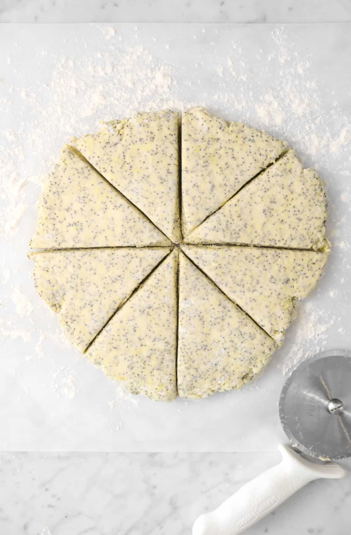 scone dough cut into eight slices on a piece of floured parchment with a pizza cutter