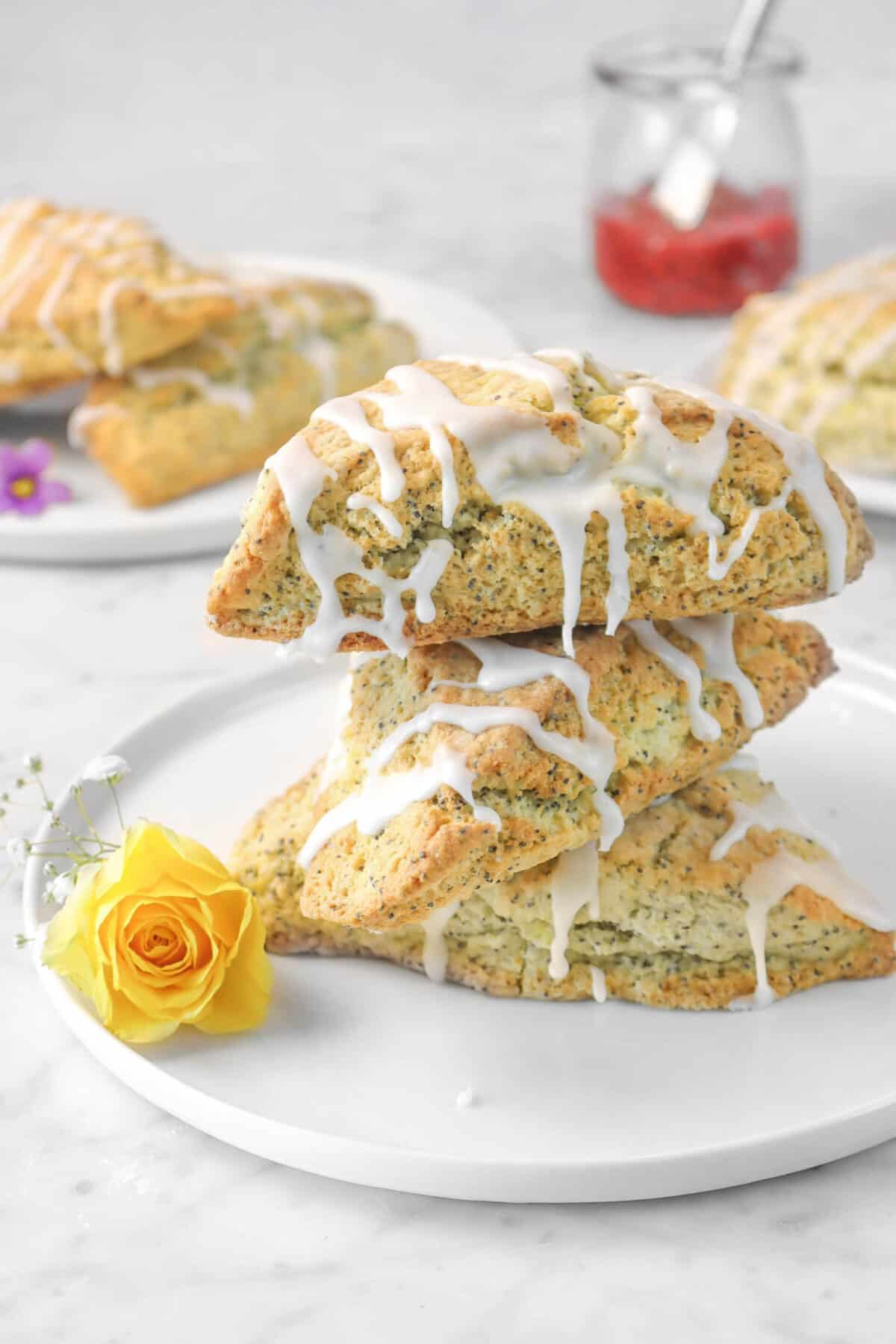 three lemon poppyseed scones with fresh flowers, more scones in the back, and a jar of jam