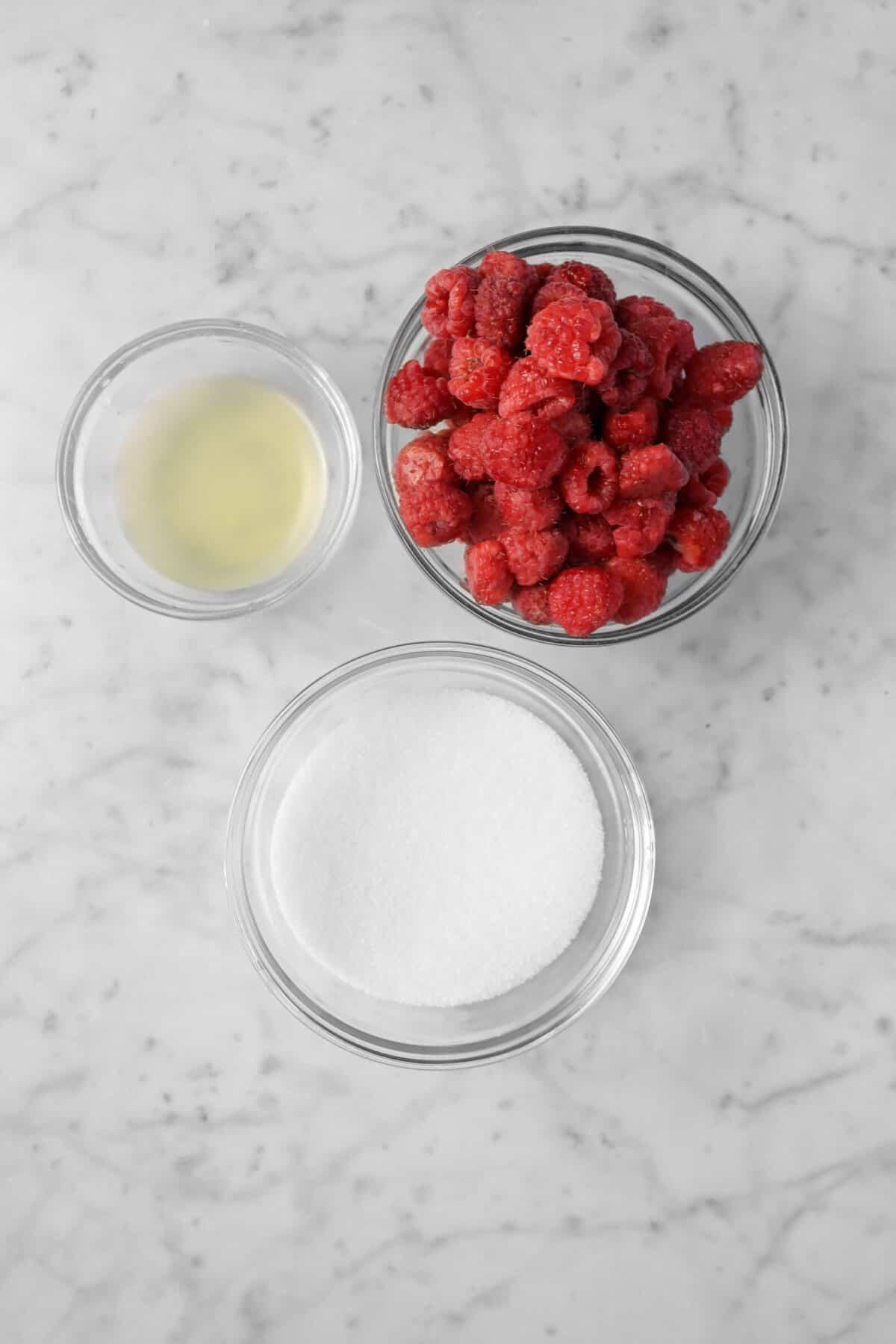 raspberries, sugar, and lemon juice in glass bowls