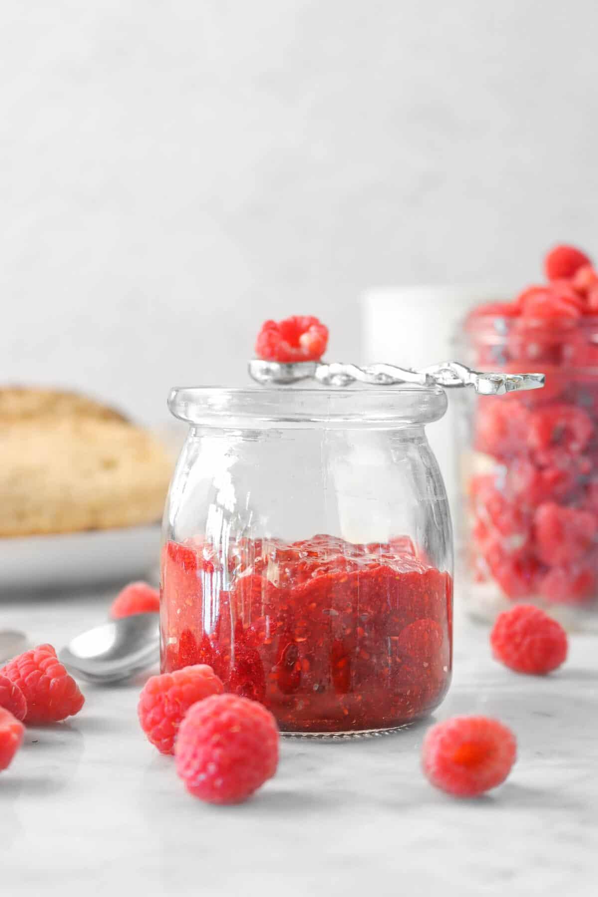 raspberry jam in a glass jar with fresh raspberries, bread, and a jar of raspberries in the background