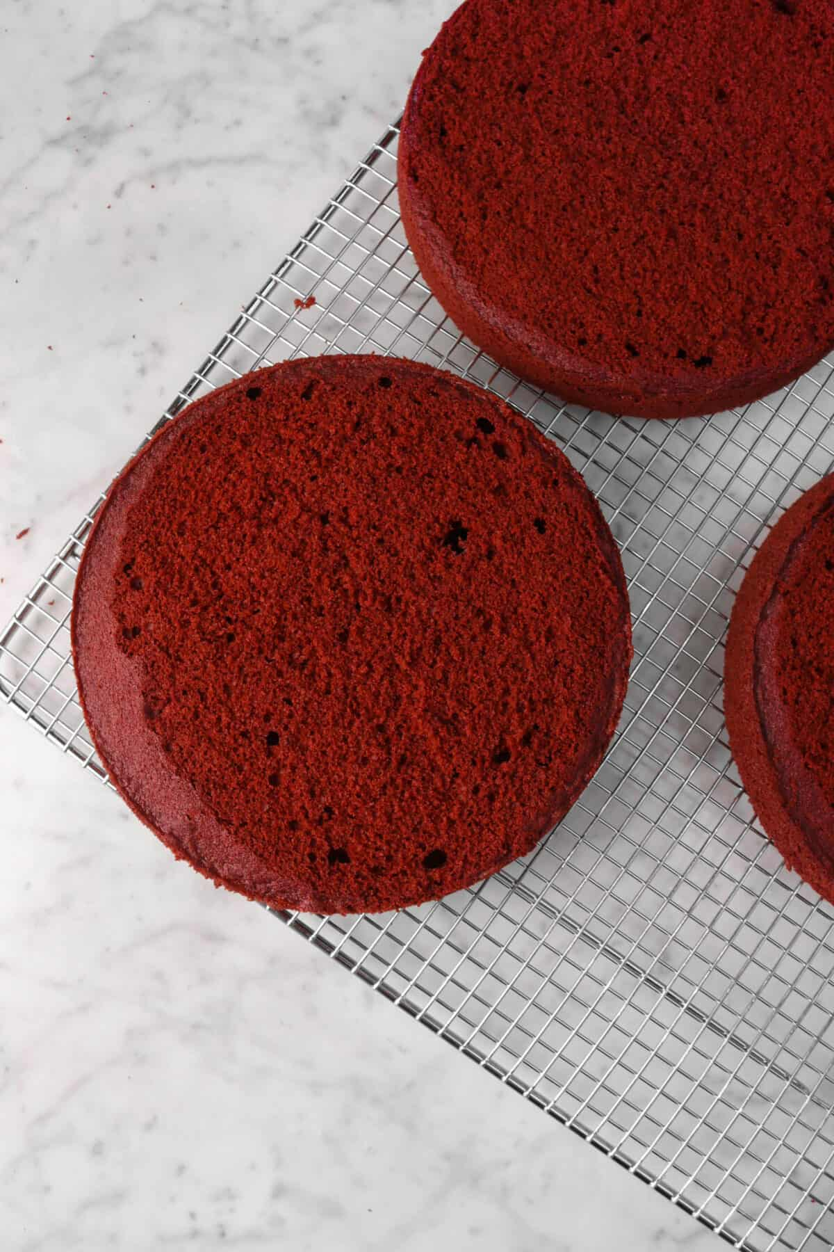 red velvet cake layers leveled on a wire cooling rack
