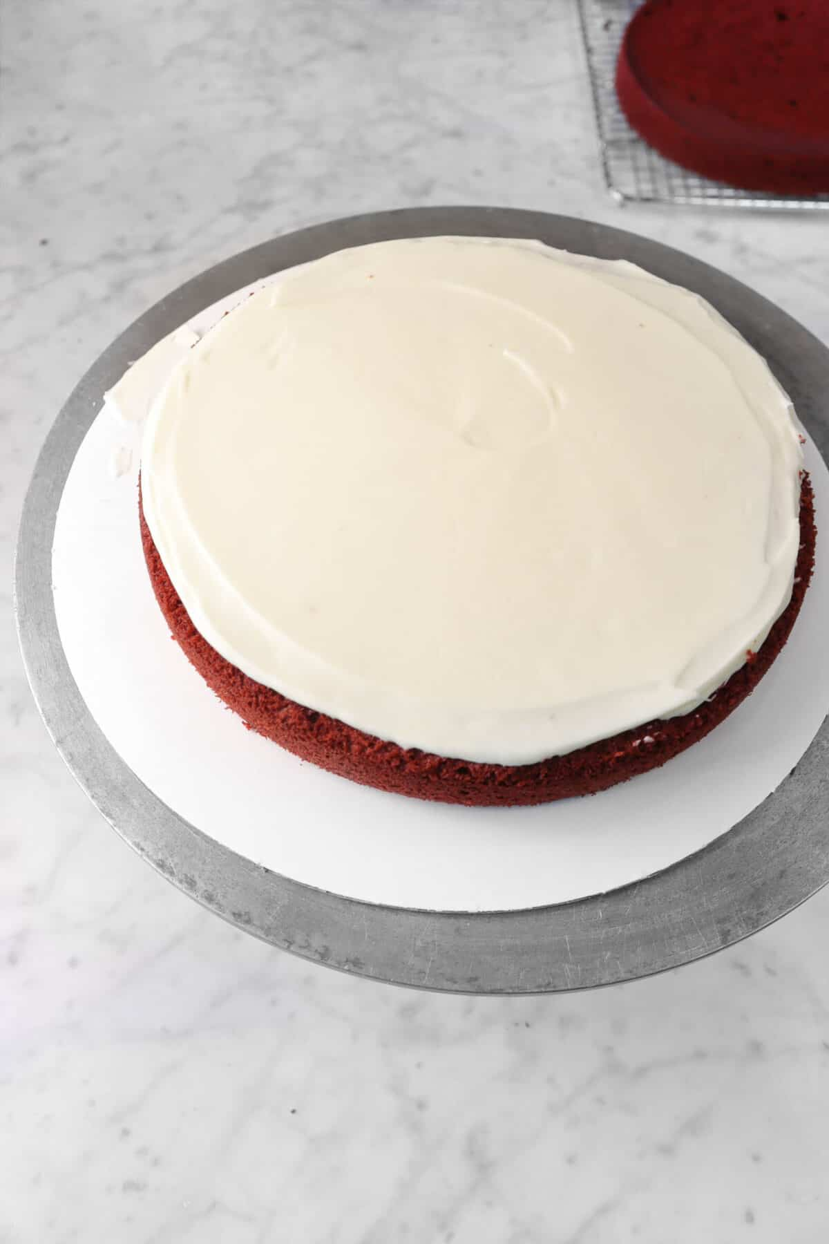 cream cheese frosting spread evenly across cake layer