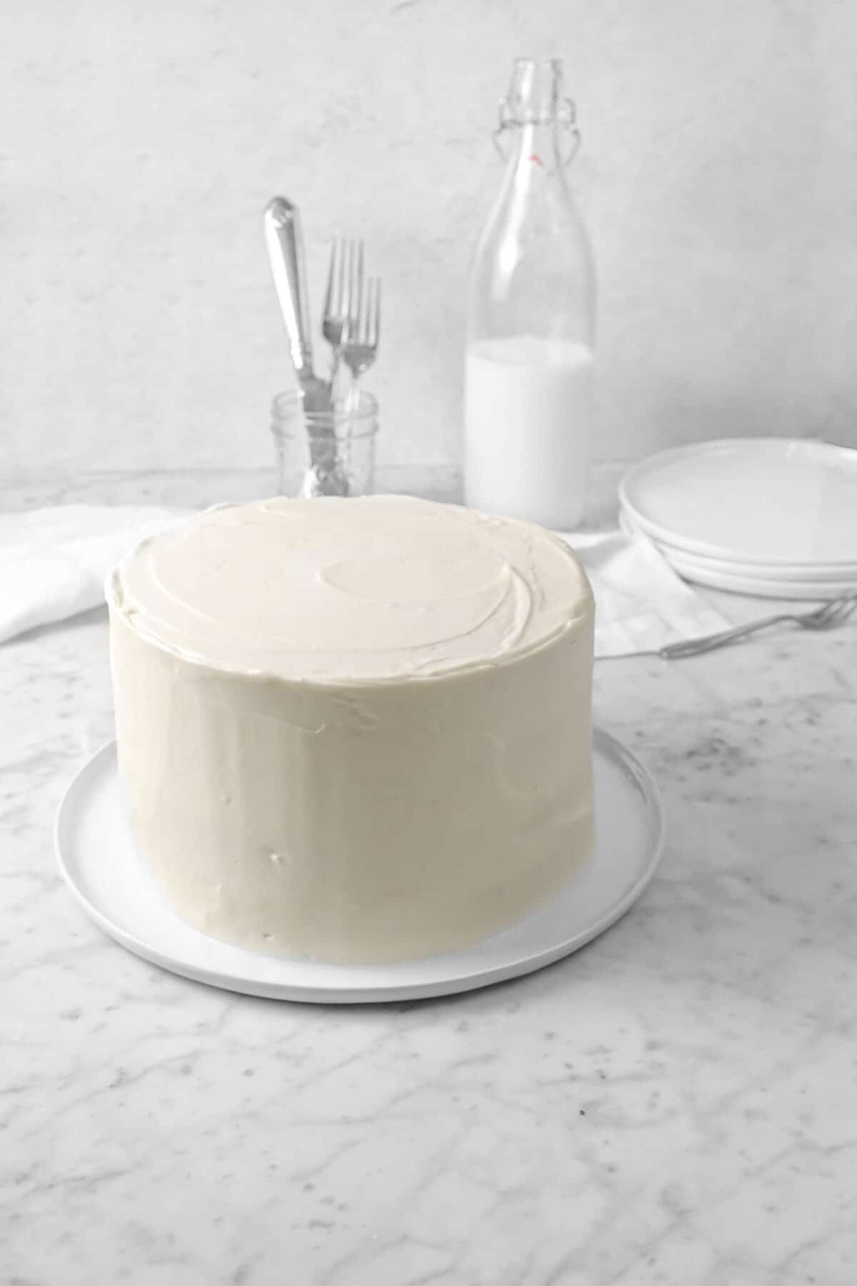 red velvet cake on a white plate with a jar of forks, a jug of milk, and a white napkin