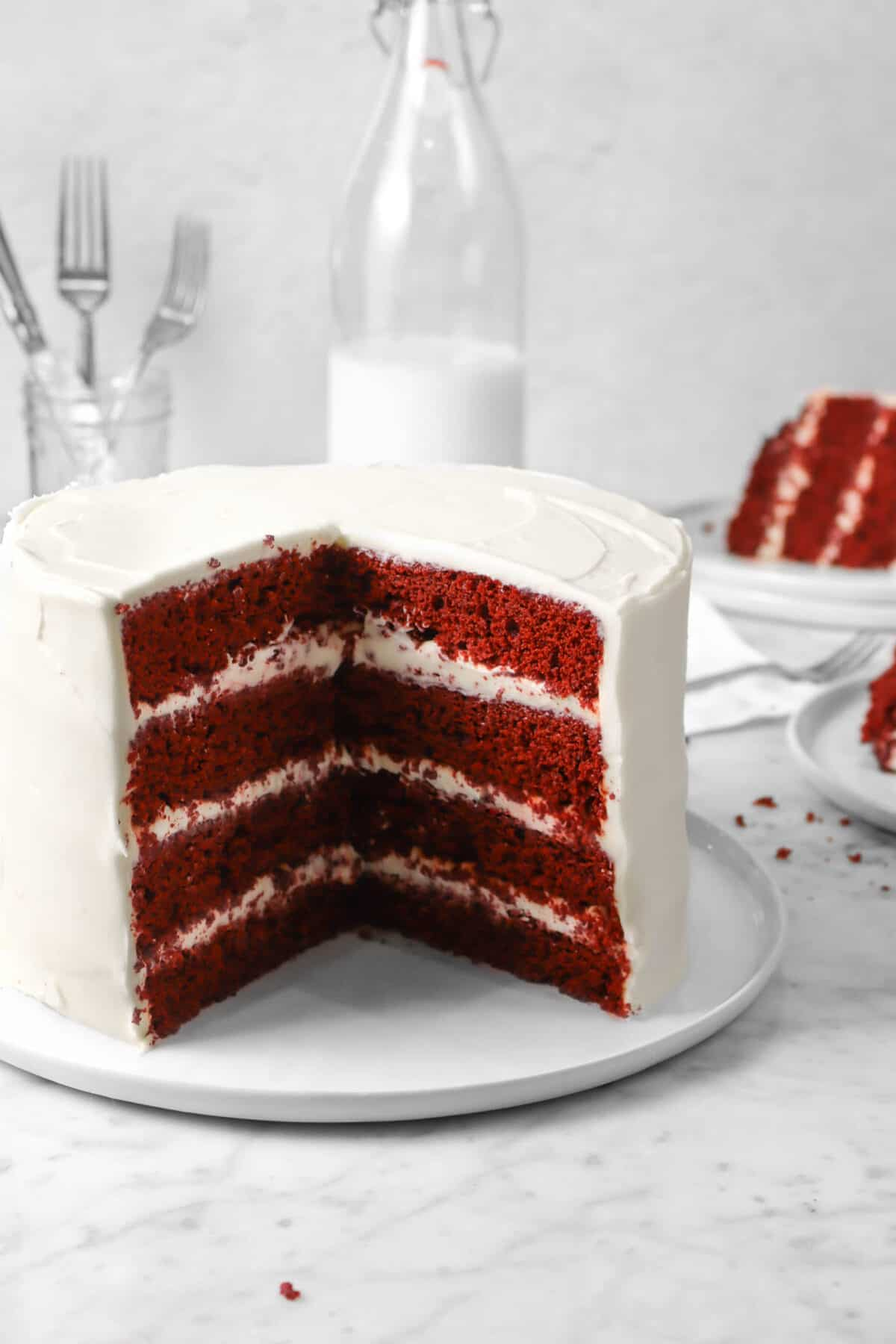 red velvet cake on a white plate with a jug of milk, a slice of cake, and a jar of forks