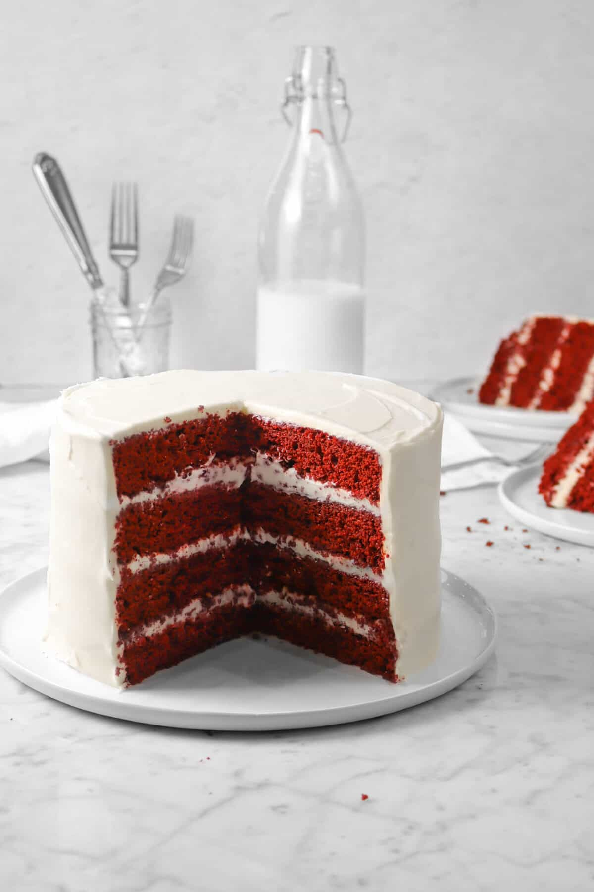 red velvet cake on a white plate with a jug of milk, a jar of forks, and two slices of cake