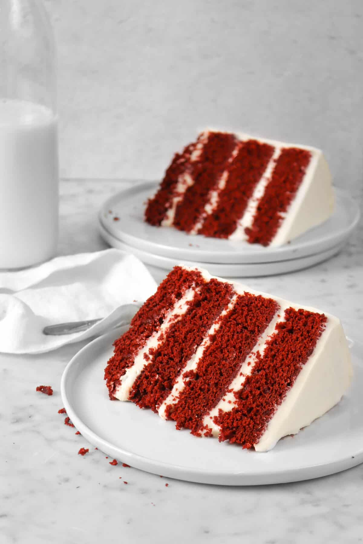 two slices of red velvet cake on white plates with a white napkin and a jug of milk