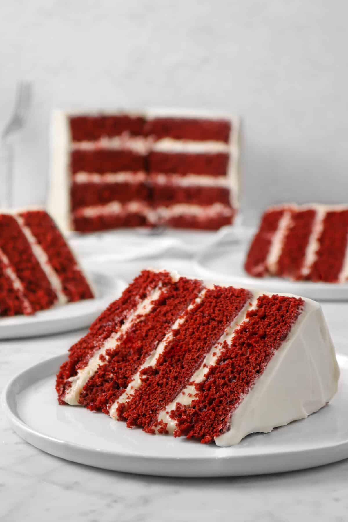 three slices of red velvet cake on white plates with the cake behind them