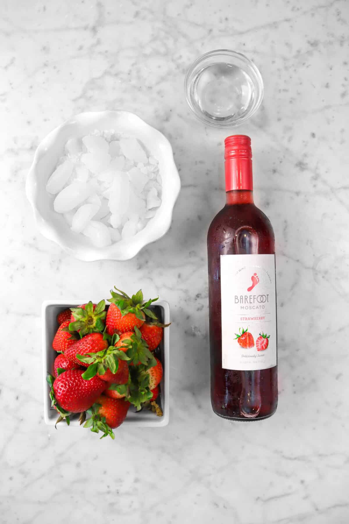 a bottle of wine, strawberries, ice, and simple syrup on a marble counter
