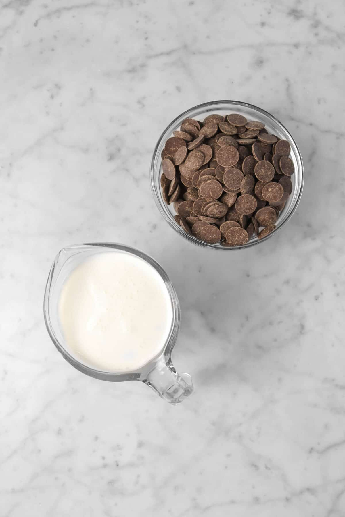 chocolate chips in a glass bowl and milk in a measuring cup