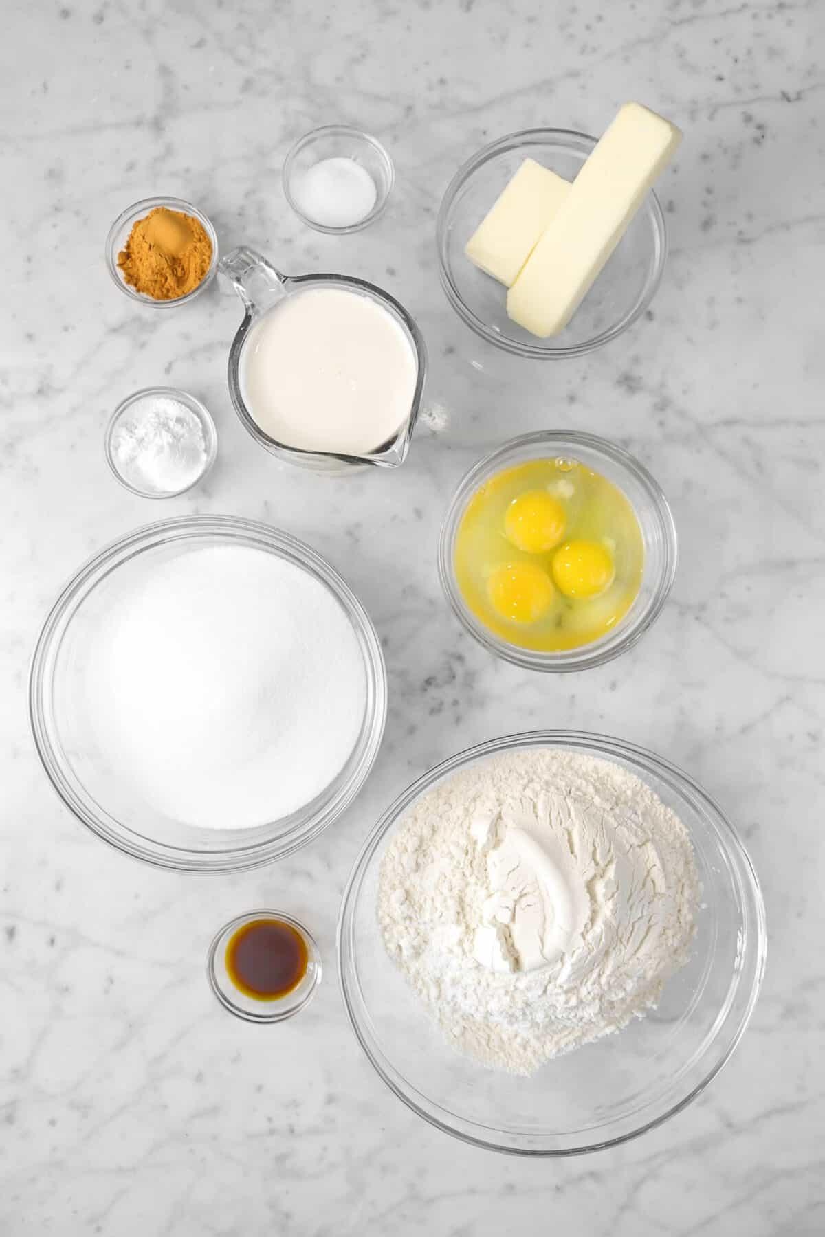 flour, eggs, sugar, vanilla, milk, baking powder, cinnamon, salt, and butter in glass bowls