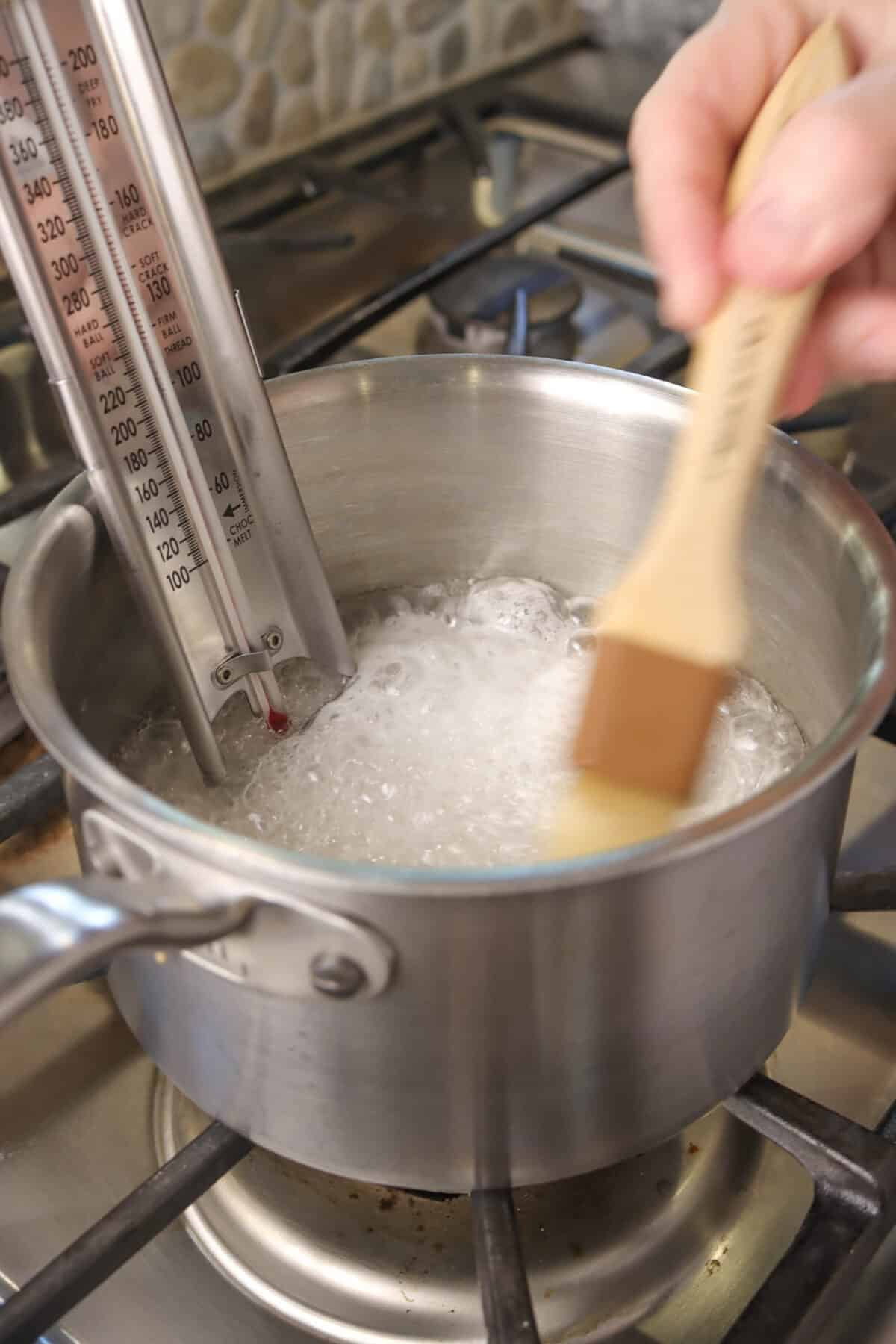 corn syrup mixture boiling with thermometer and sides being brushed down