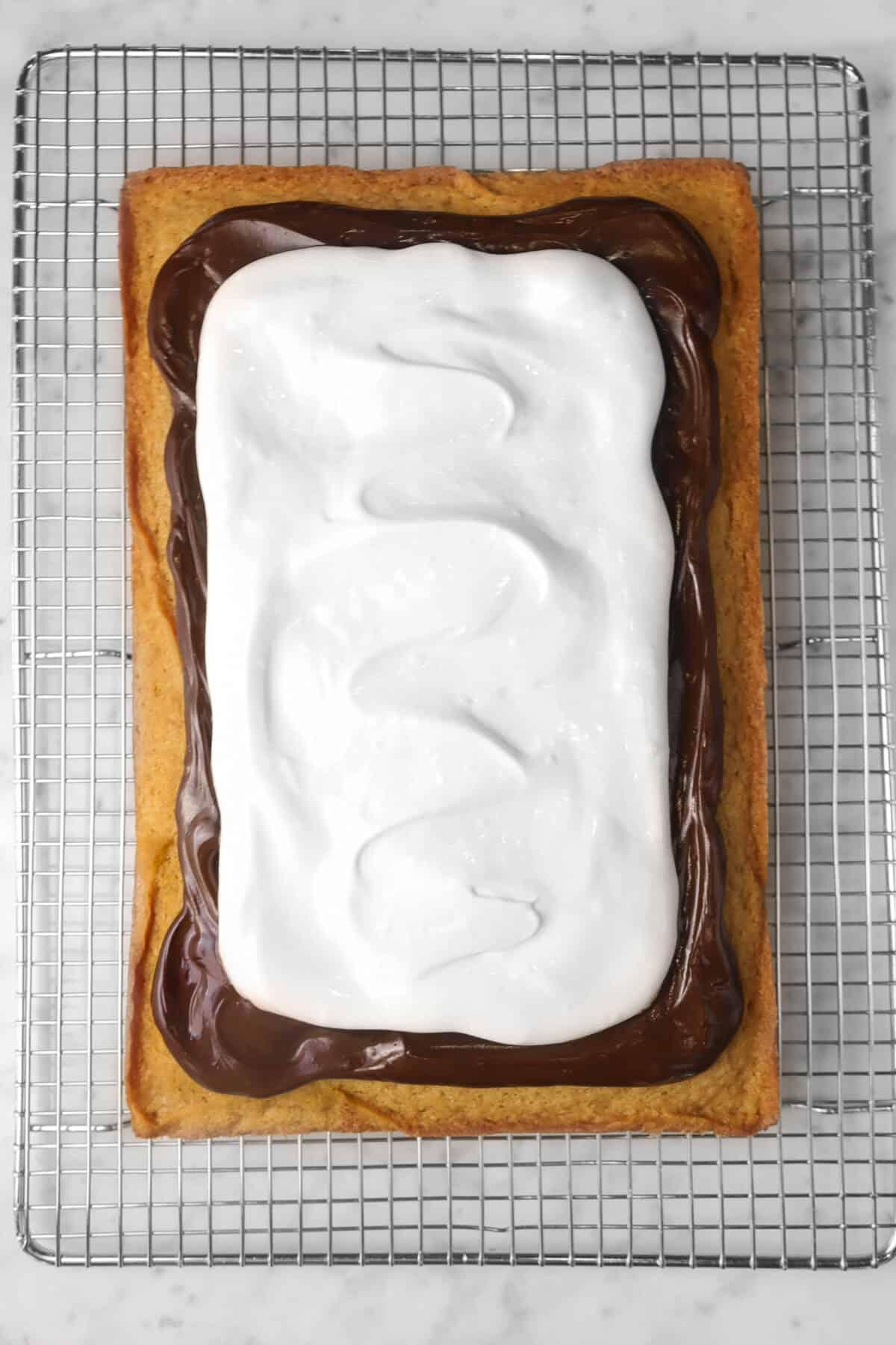 marshmallow fluff spread on top of ganache on cinnamon cake