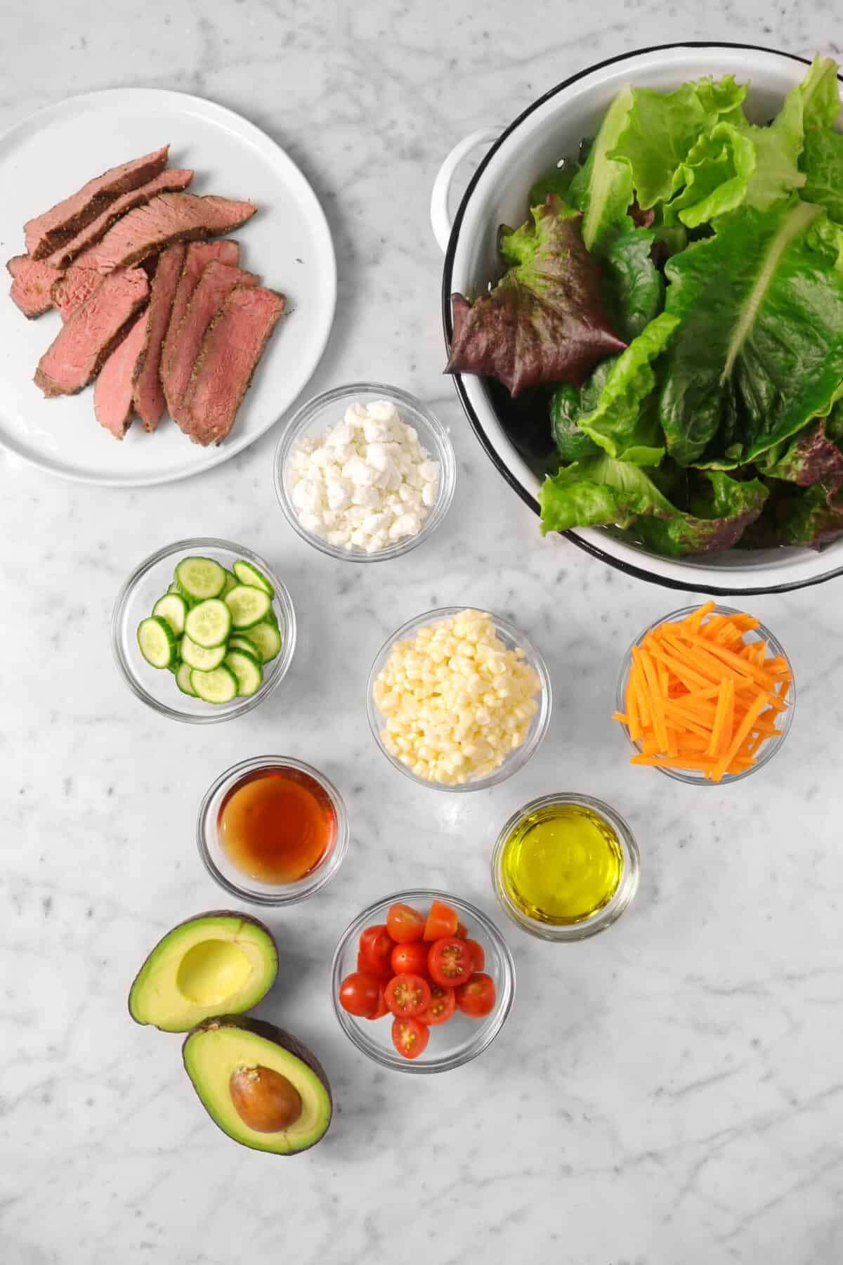 lettuce, julienned carrots, olive oil, sliced tomatoes, avocado, red wine vinegar, corn, sliced cucumbers, goat cheese, and steak on a marble counter