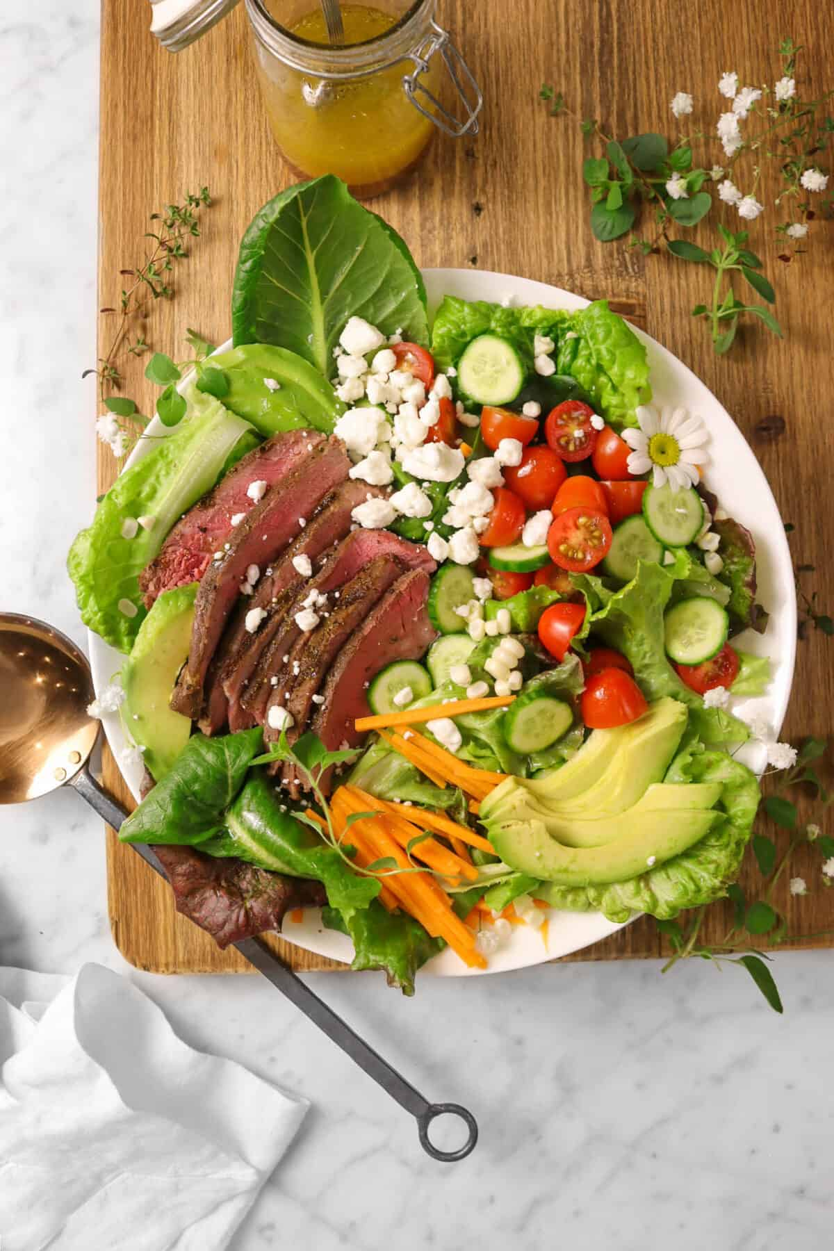 steak salad with white flowers, herbs, a copper serving spoon and a white napkin on a wood board