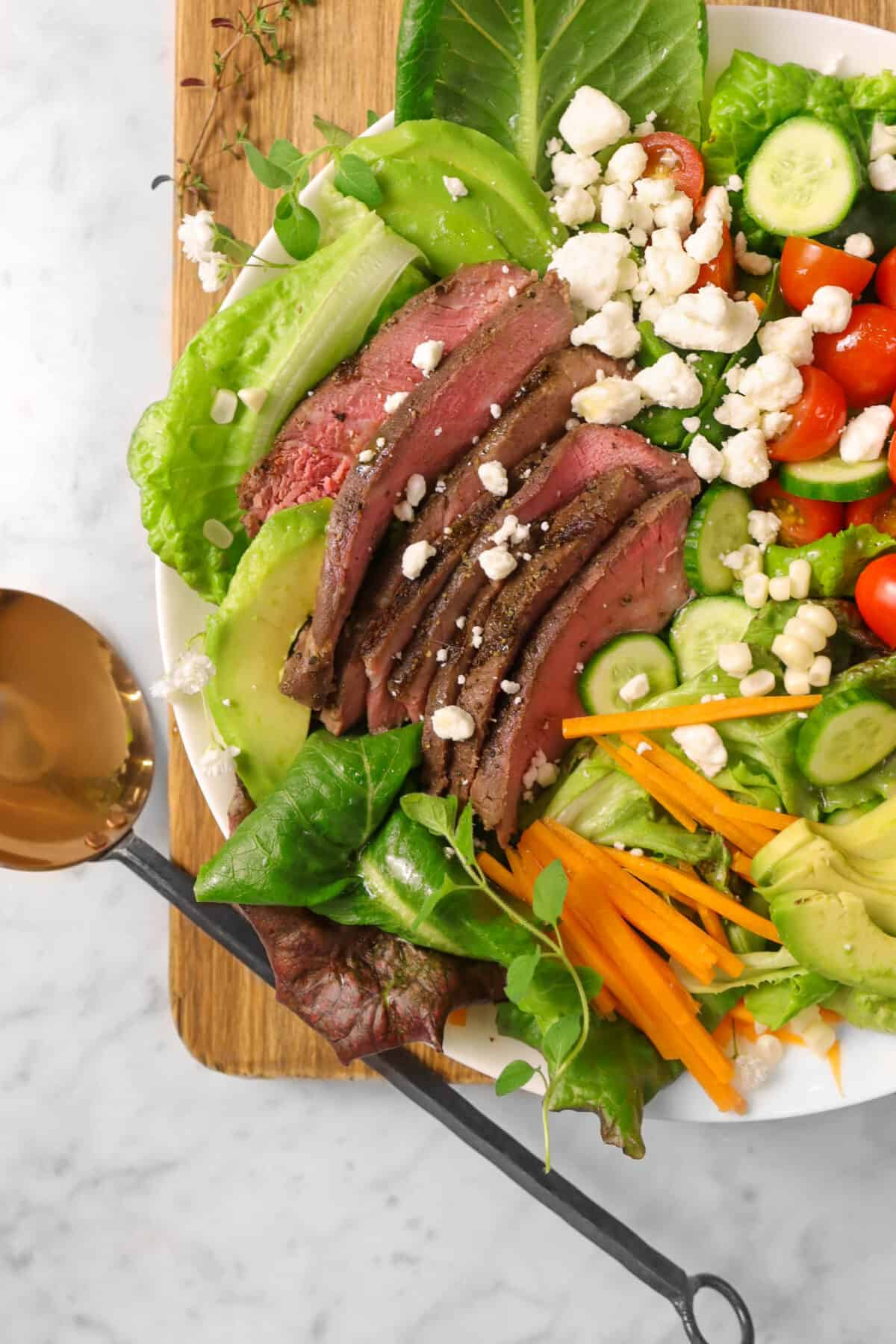 steak salad on a wood board with fresh herbs, flowers, and a copper serving spoon