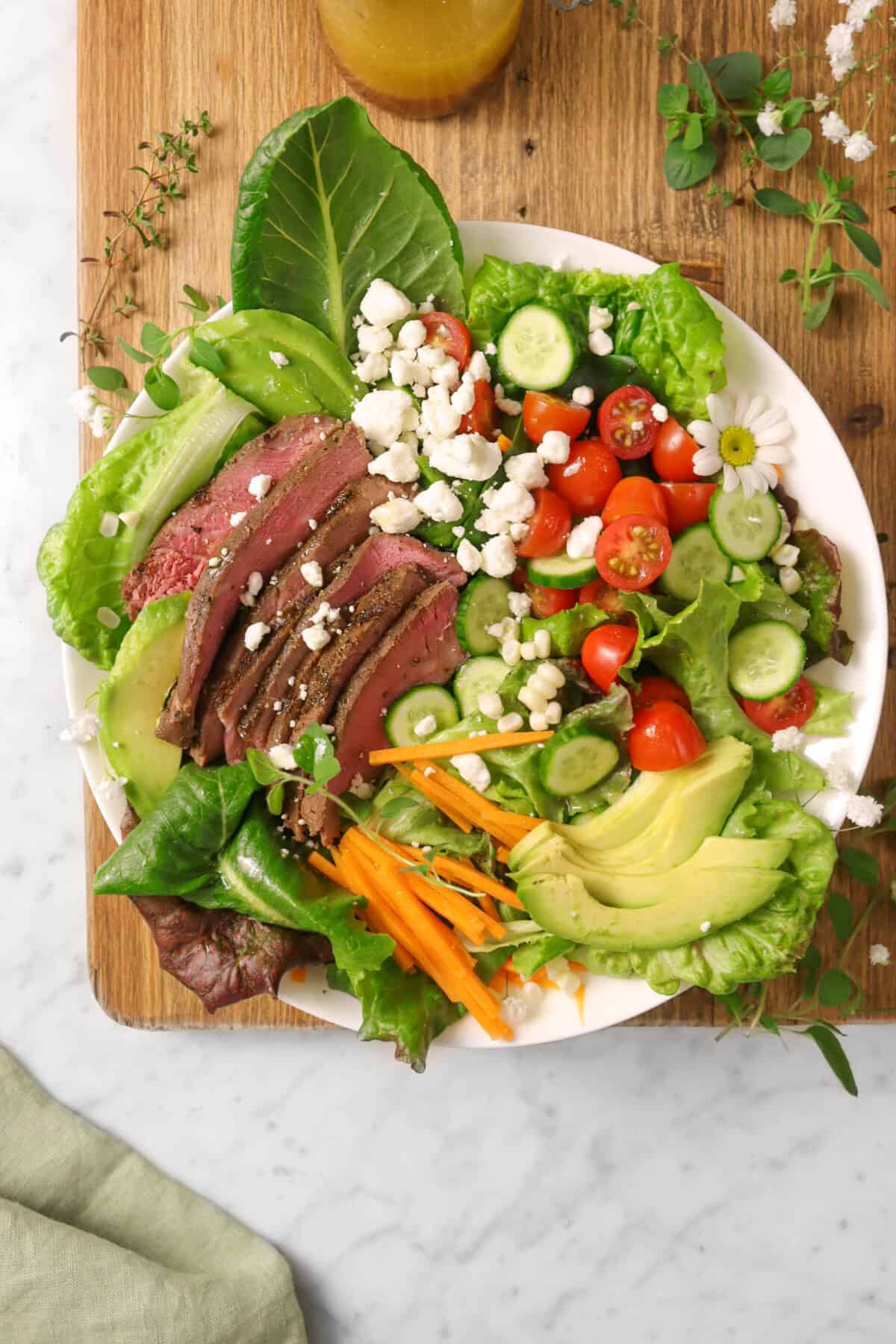 steak salad in a white bowl with herbs, flowers, a green napkin, on a wood board
