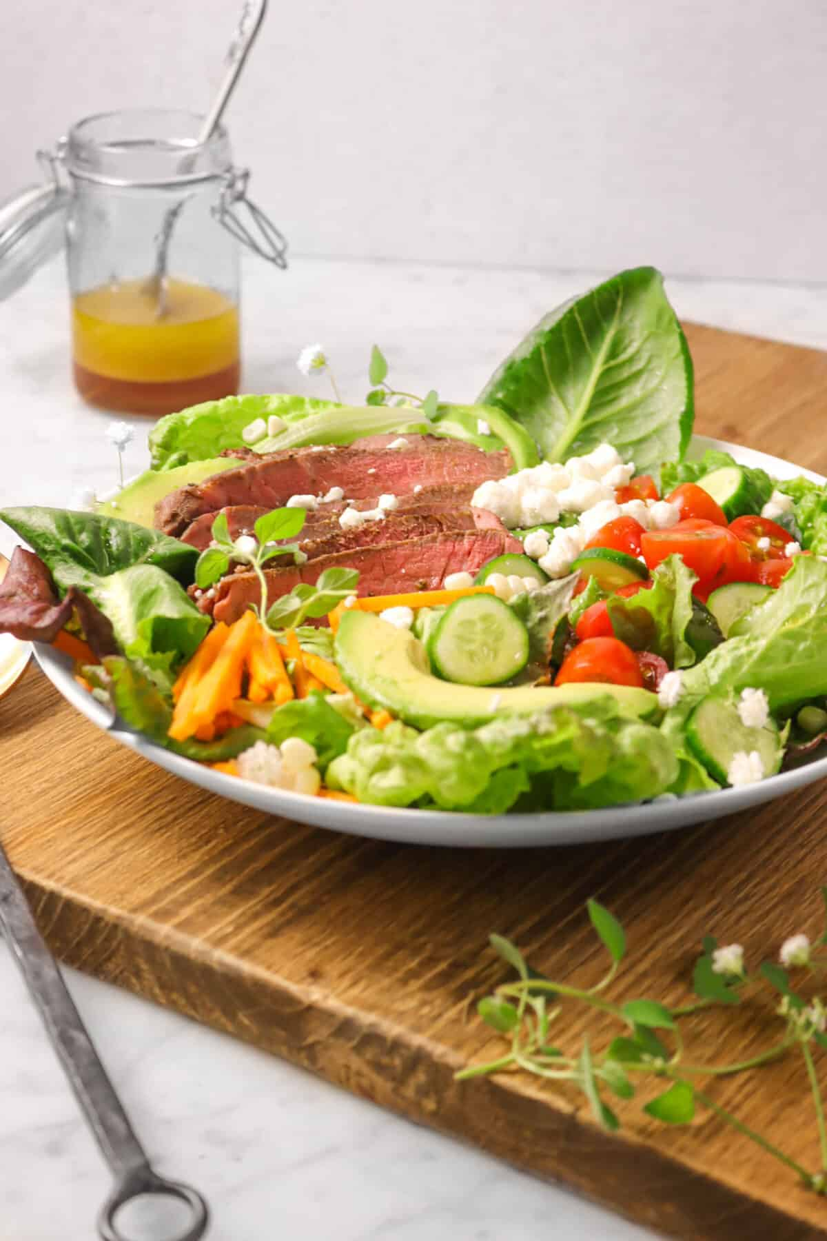 steak salad on a wood board with fresh herbs and a jar of red wine vinaigrette