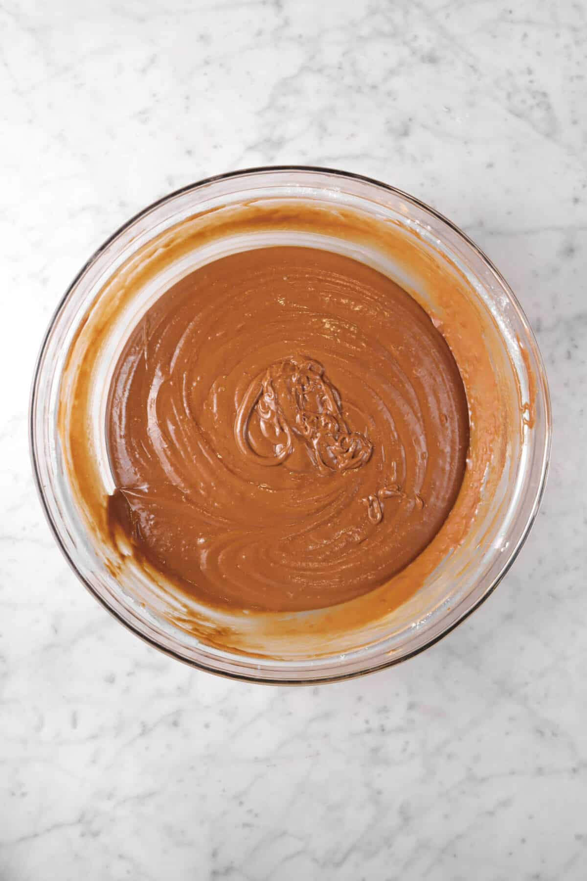 chocolate cupcake batter in a glass bowl on a marble counter
