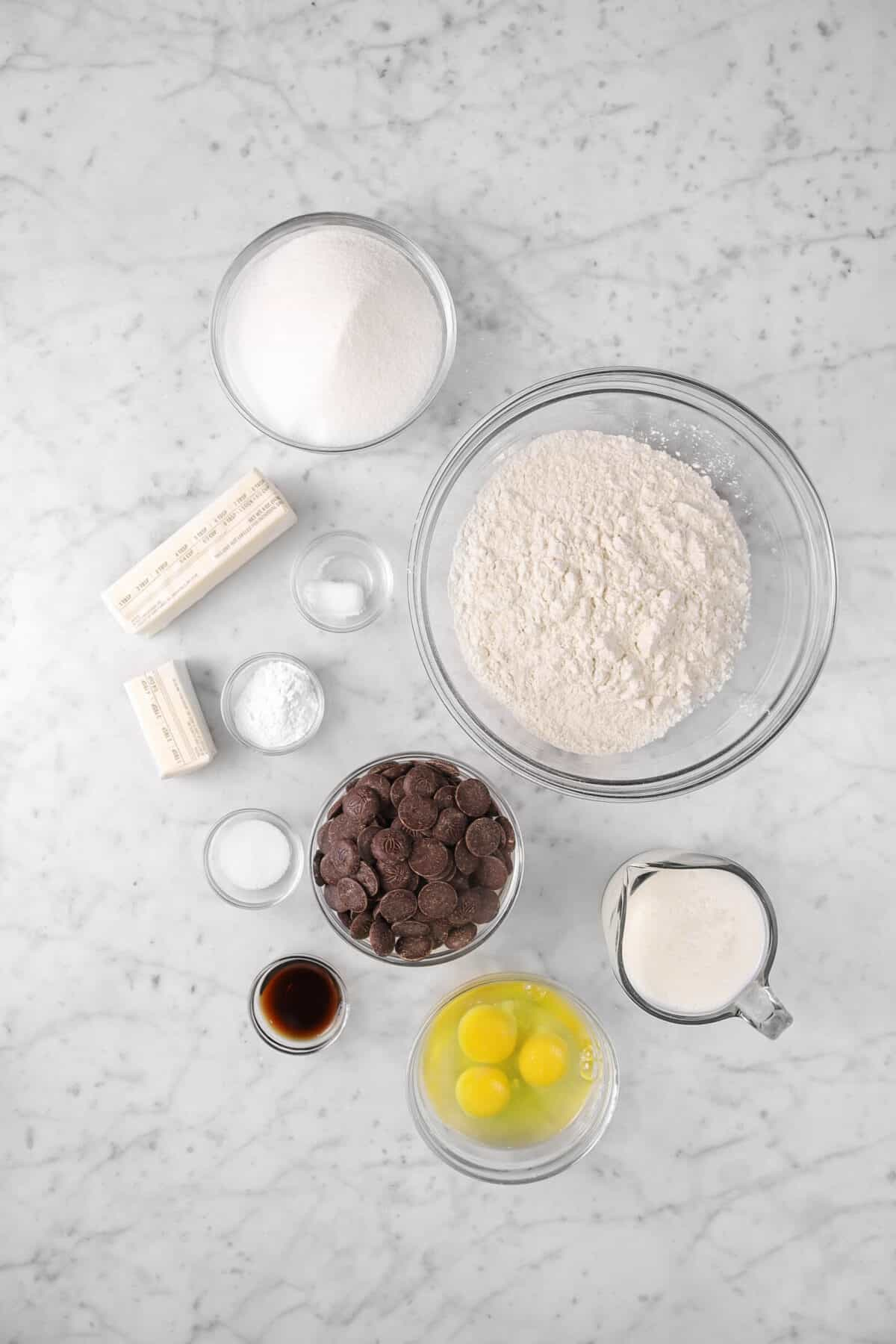 sugar, flower, butter, salt, baking soda, baking powder, chocolate, vanilla, eggs, and milk on a counter
