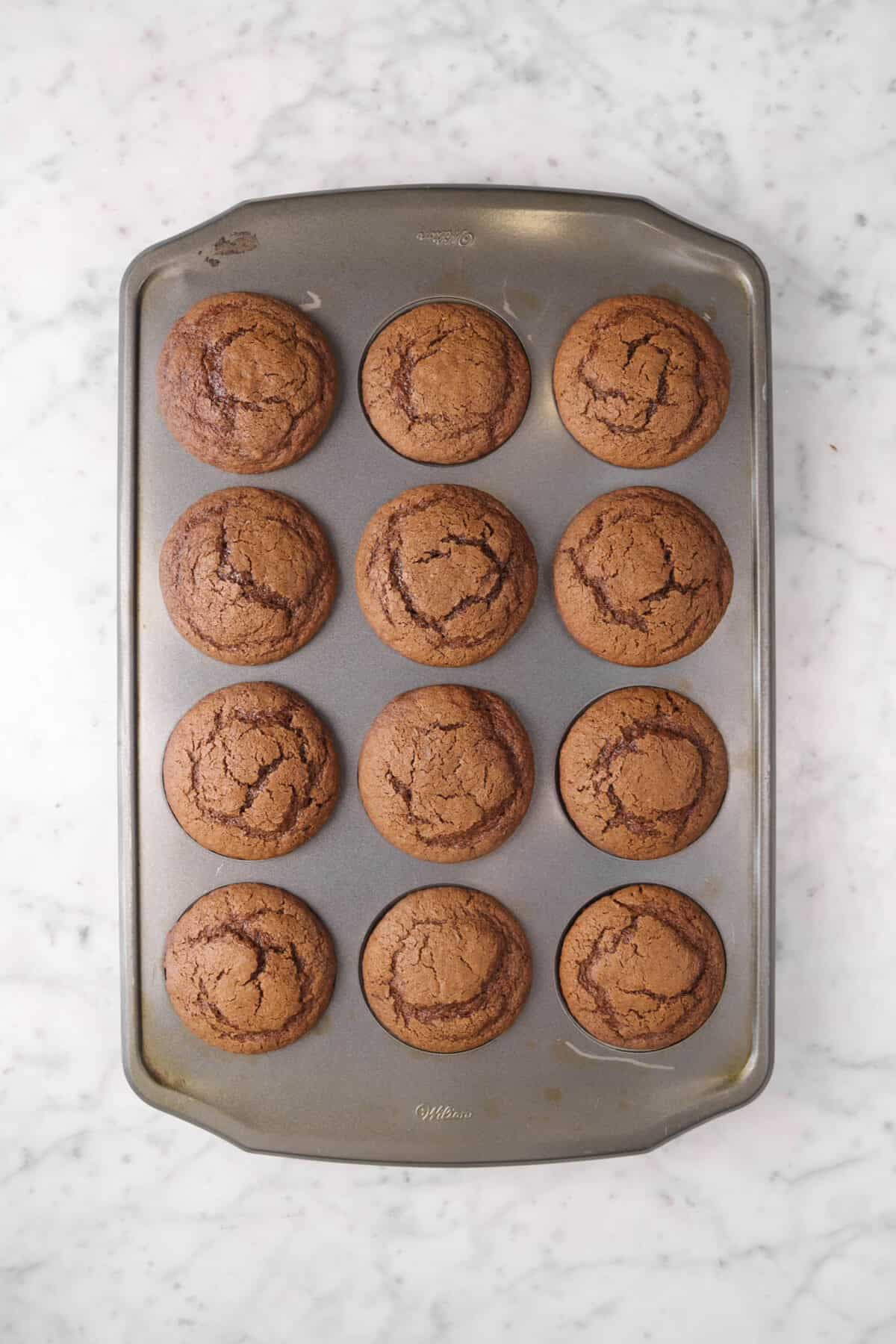 twelve chocolate cupcakes in a muffin pan