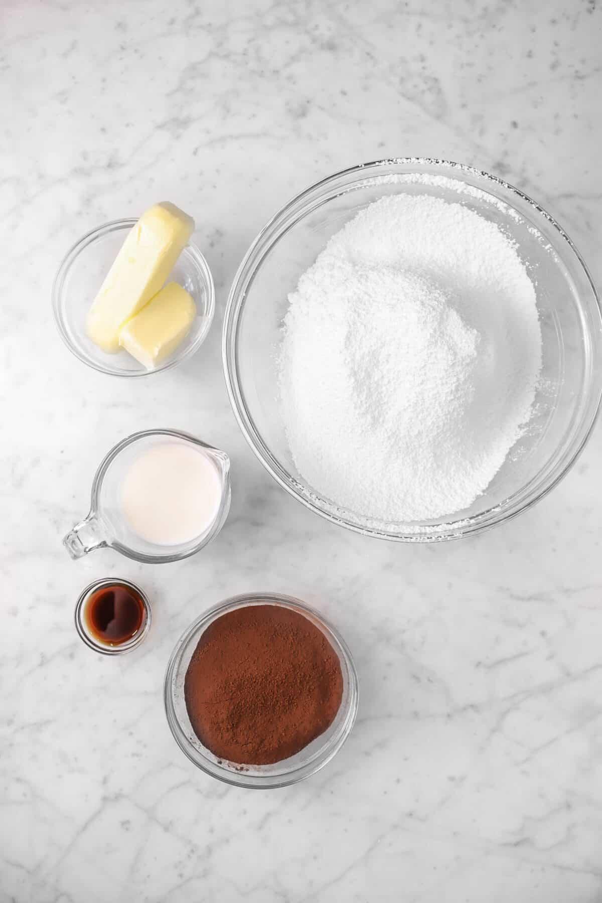 butter, milk, vanilla, cocoa powder, and powdered sugar on a counter