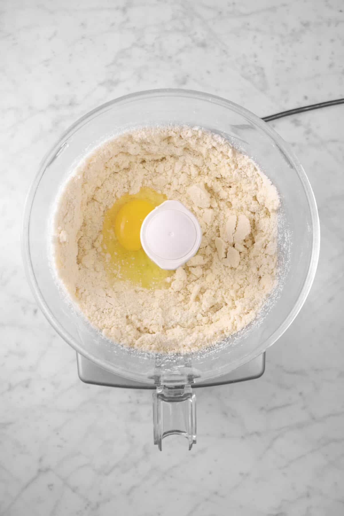 egg added to flour mixture in food processor