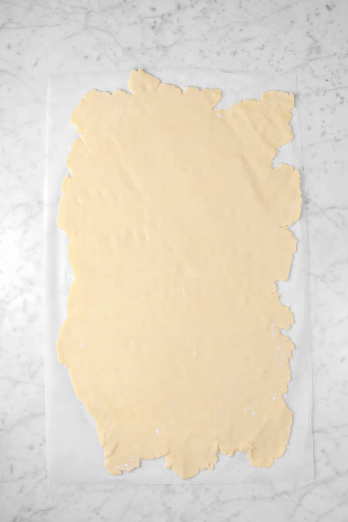 pie dough rolled out onto a large piece of parchment