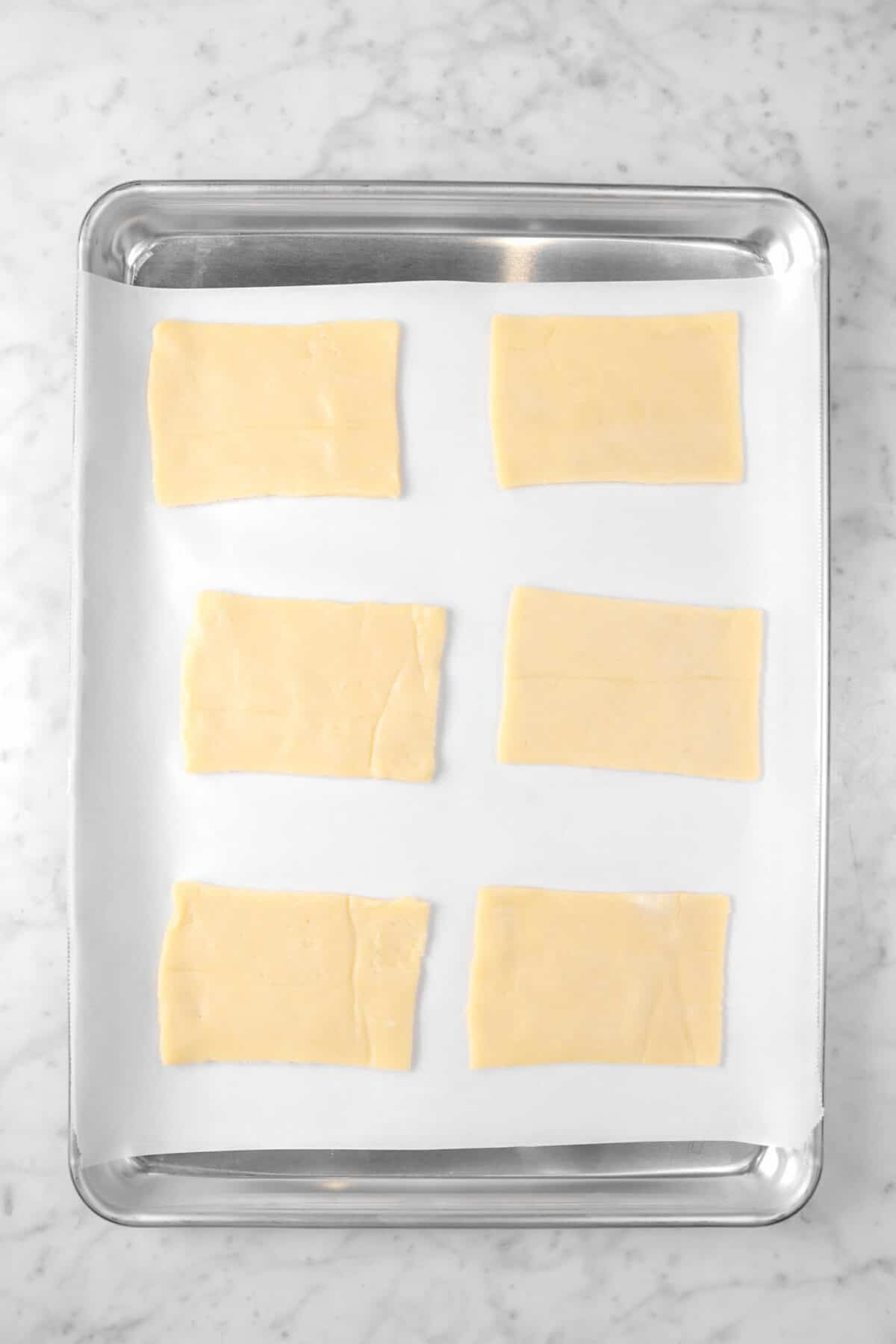 six rectangles of pie dough on a sheet pan with parchment paper