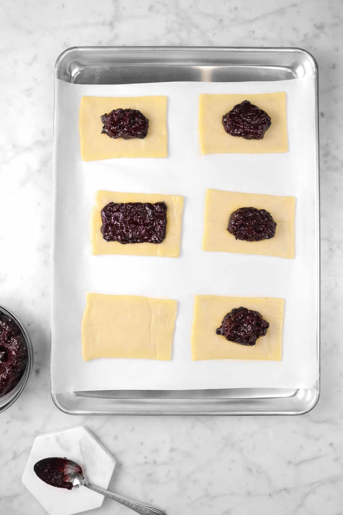 six pieces of pie dough on a sheet pan with five having jam in the center