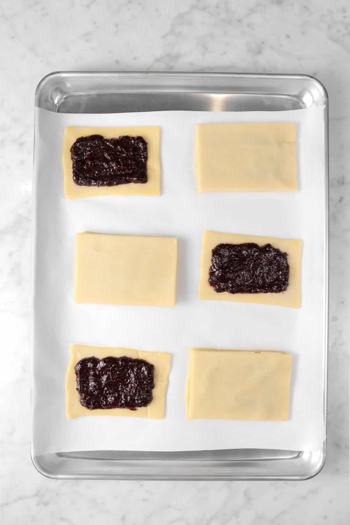 six pop tarts on a sheet pan with three covered and three not covered