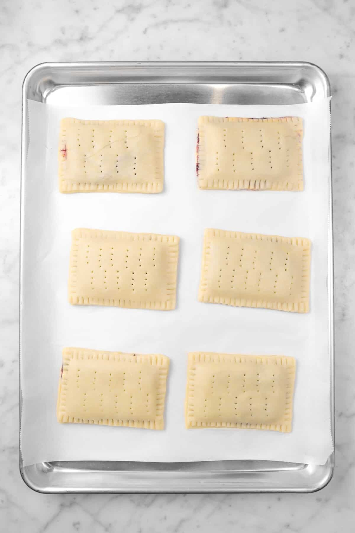 six pop tarts on a sheet pan with parchment paper