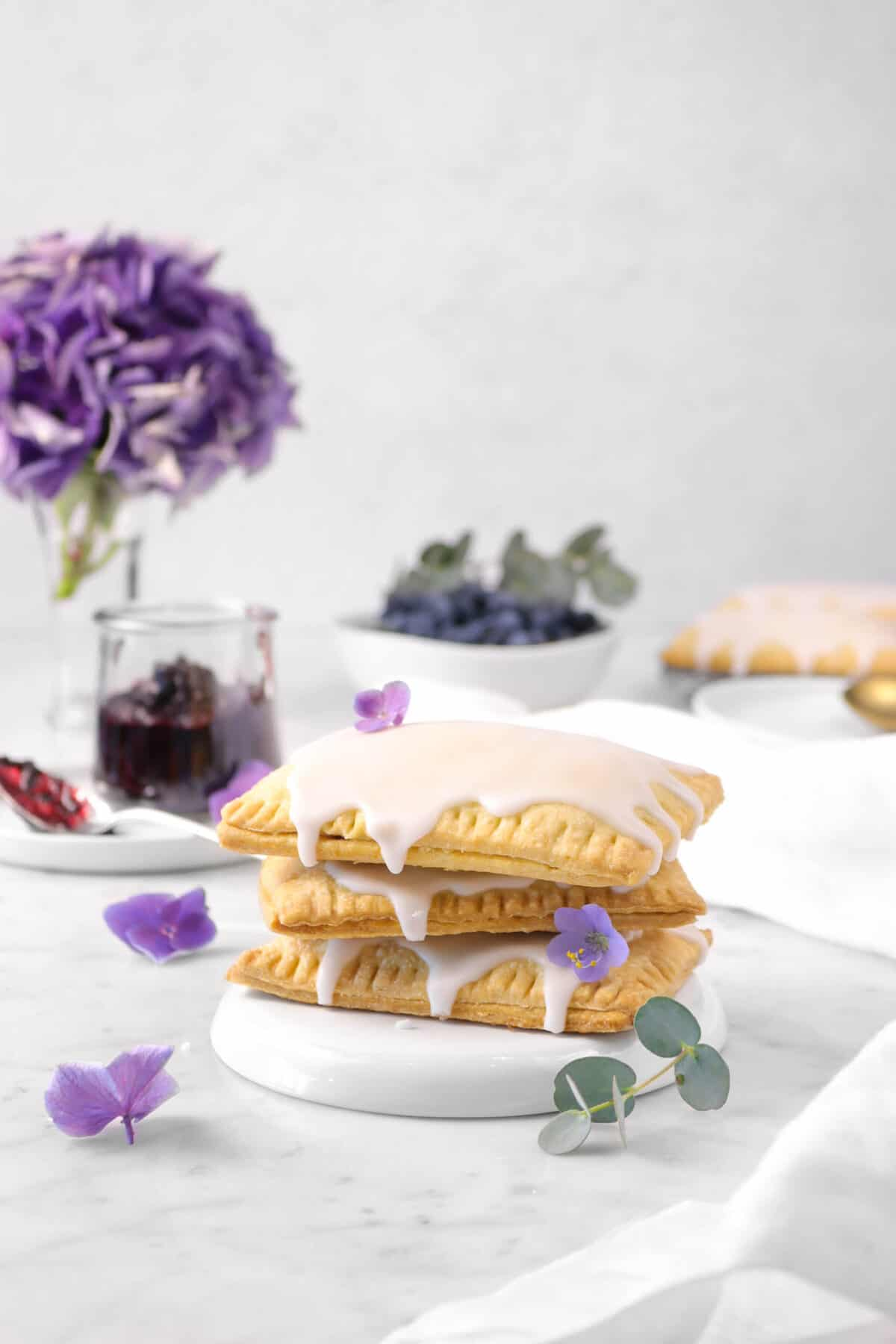 three pop tarts stacked with purple flowers, a napkin, a jar of jam, eucalyptus, a bowl of blueberries, and more pop tarts behind