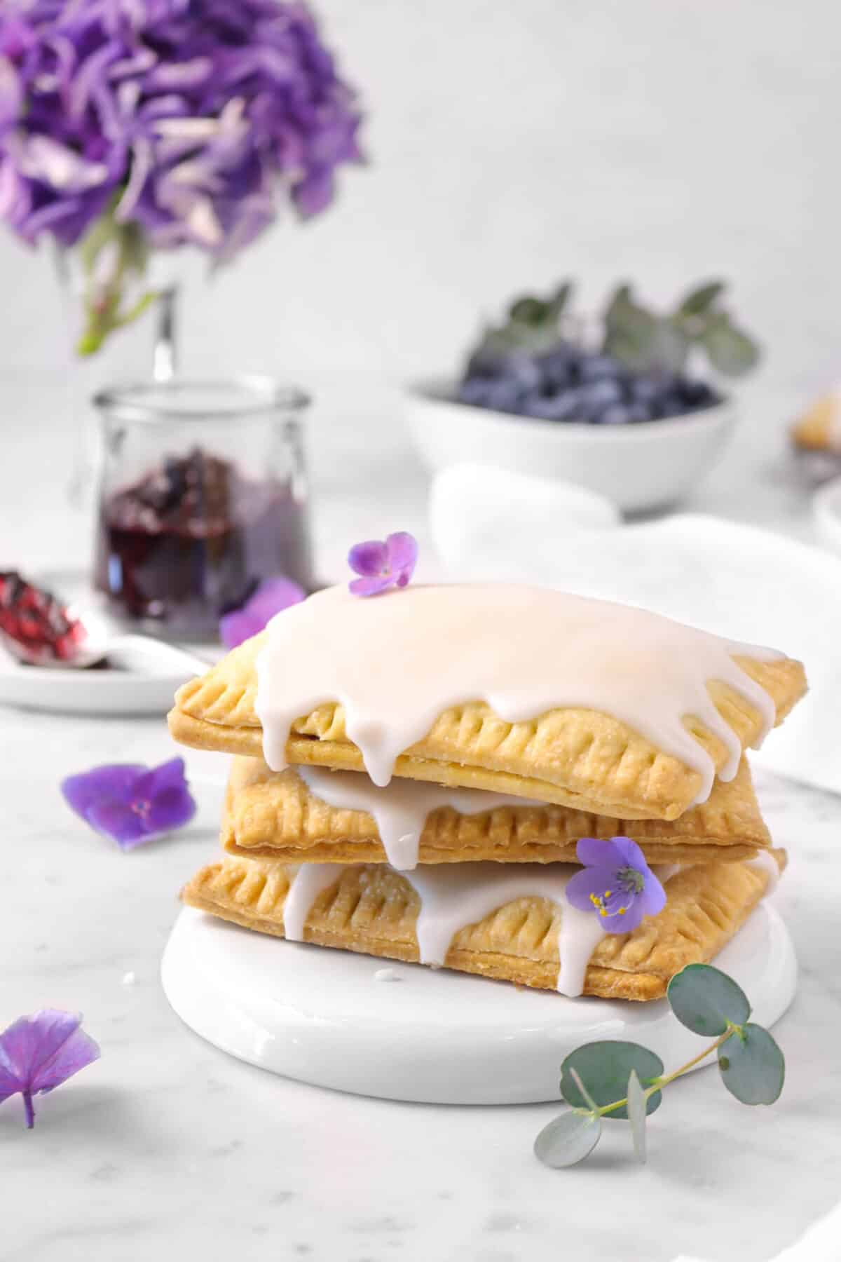 pop tarts stacked with flowers on a white plate, a jar of blueberry jam, a messy spoon, and a bowl of blueberries