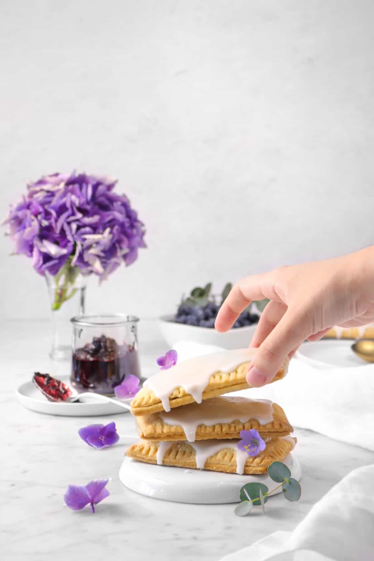 a hand grabbing a pop tart off a stack with flowers, jam, and blueberries in the background
