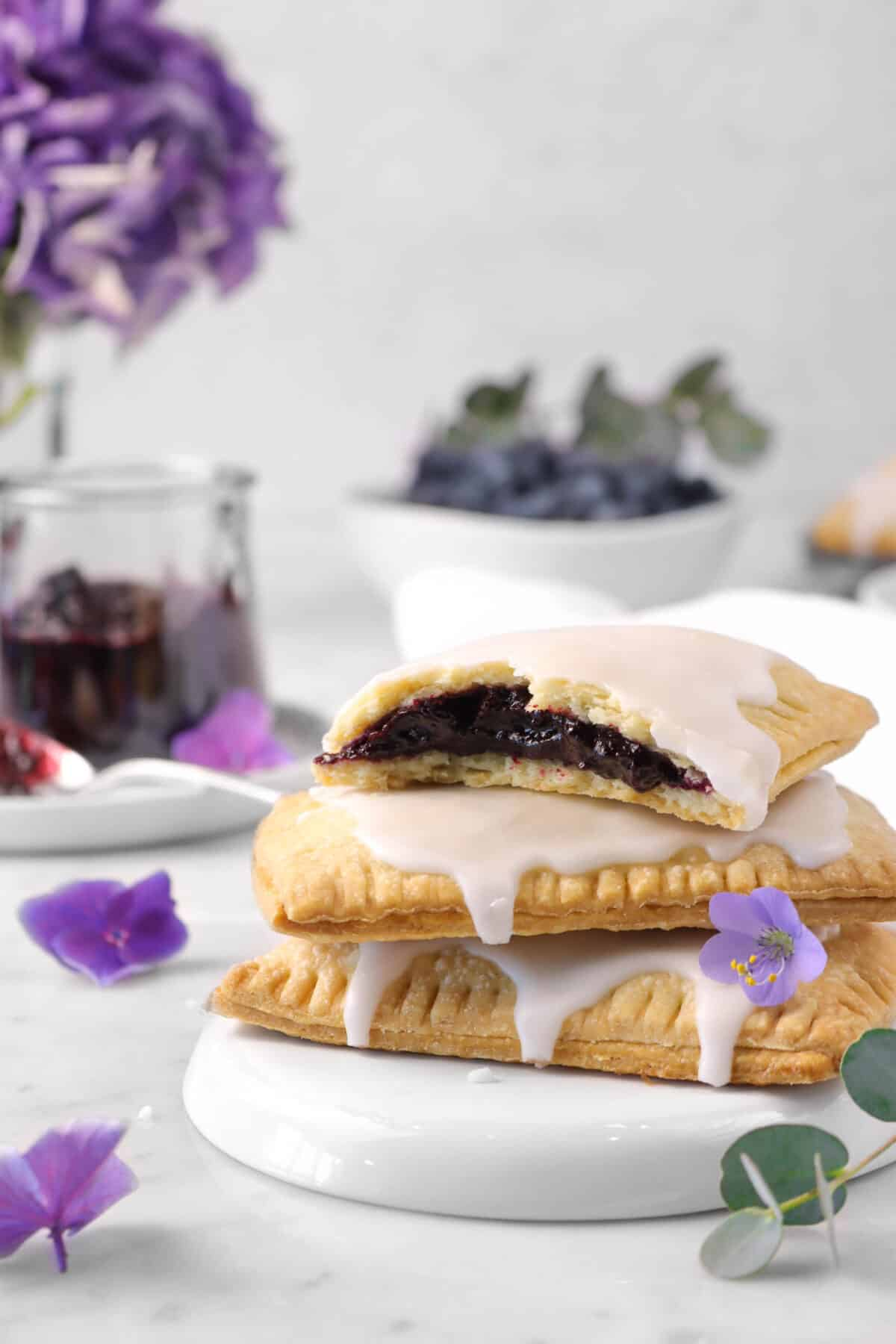 three stacked pop tarts with one broken open, flowers, and jam