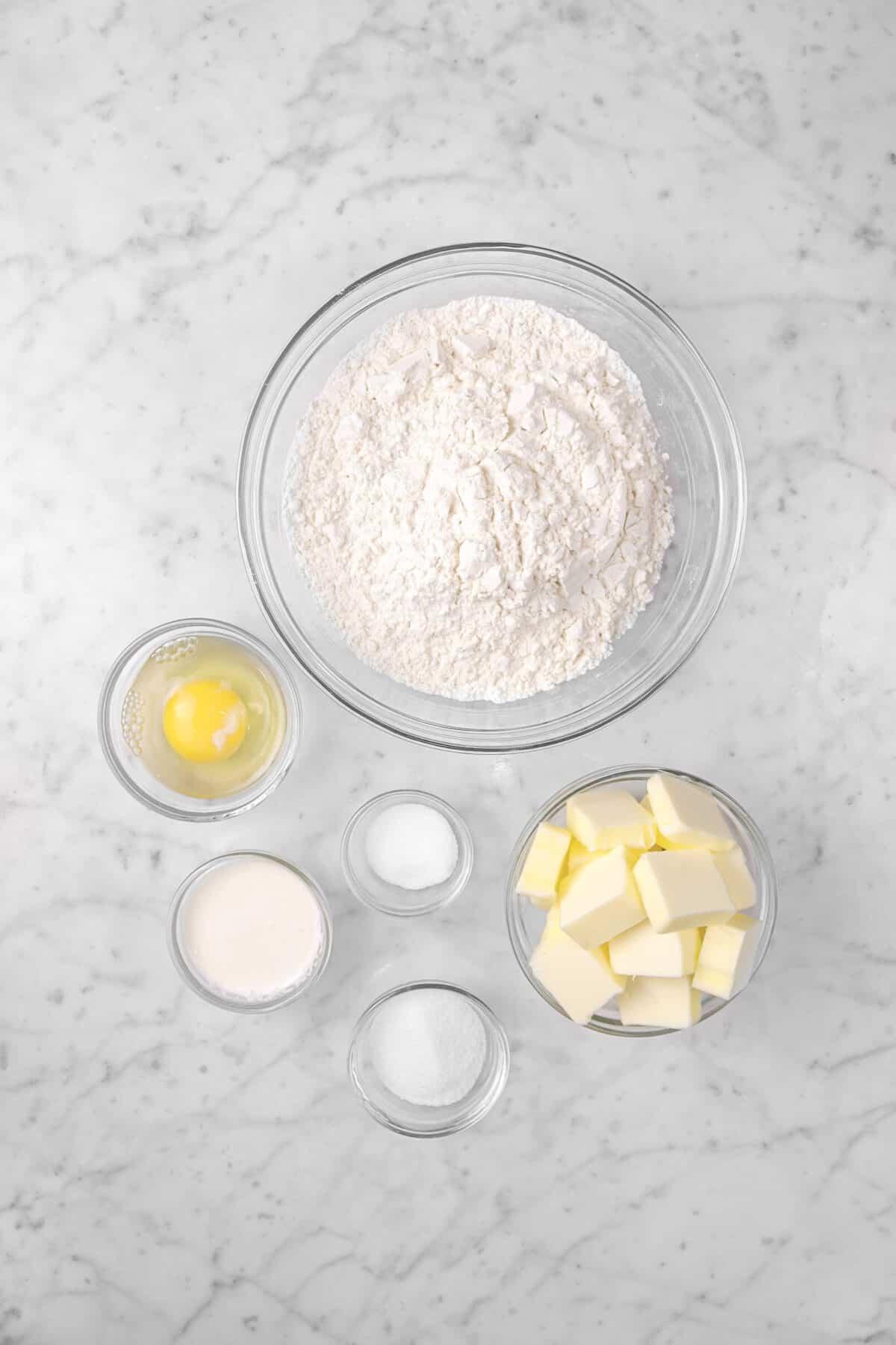 flour, an egg, milk, salt, sugar, and butter on a marble counter
