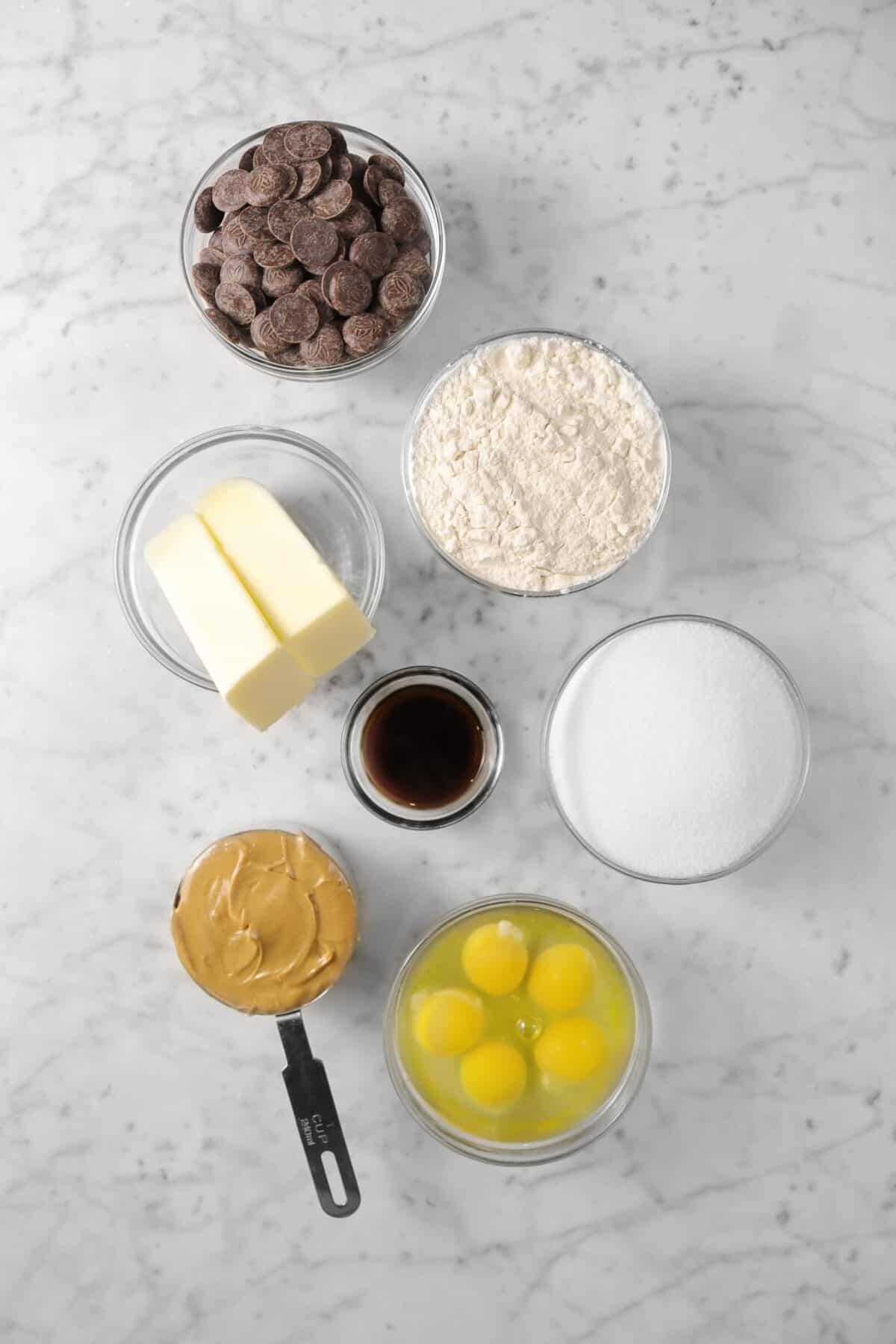 chocolate, flour, butter, vanilla, sugar, eggs, and peanut butter on a marble counter