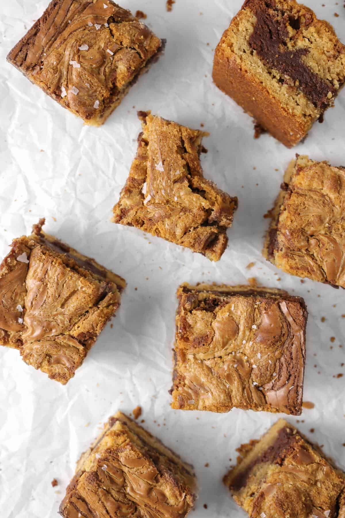 eight brownies on parchment paper with a bite taken out of one