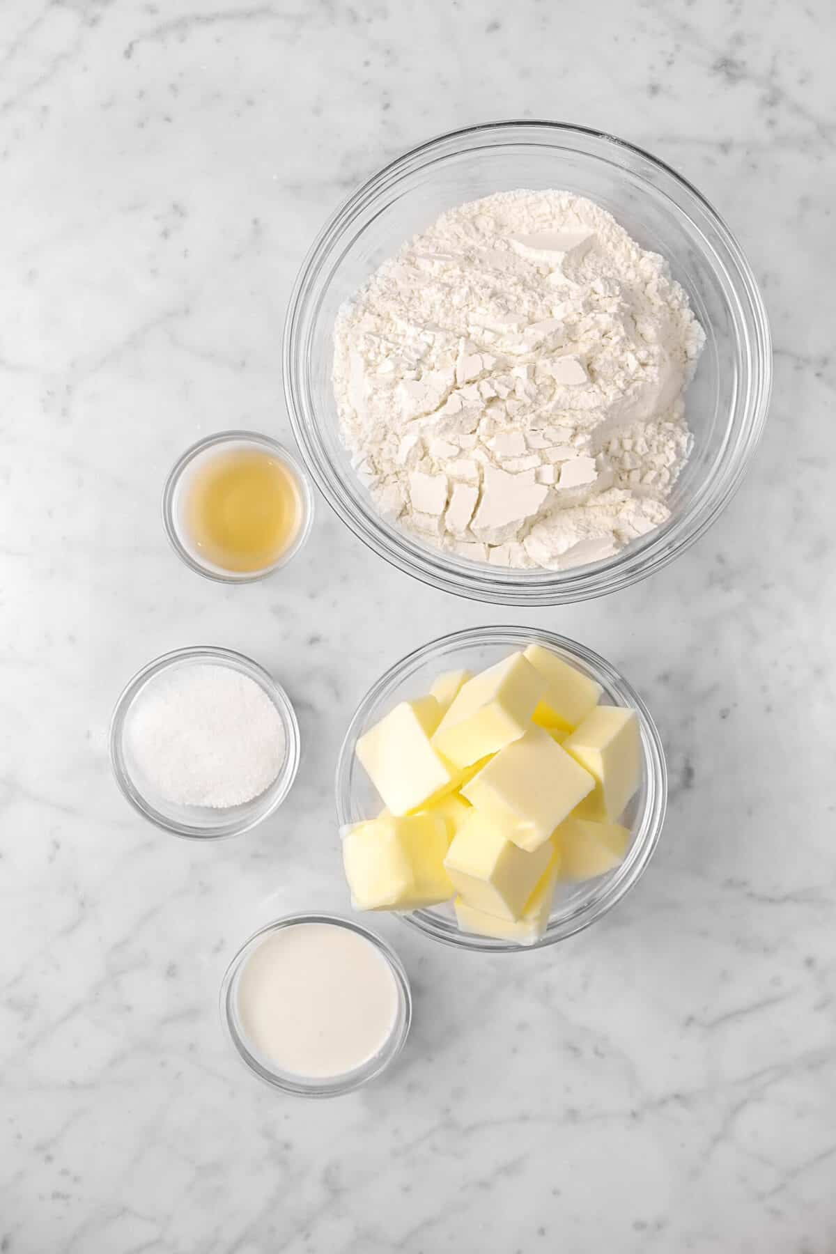flour, apple cider vinegar, sugar, butter, and cream on a marble counter