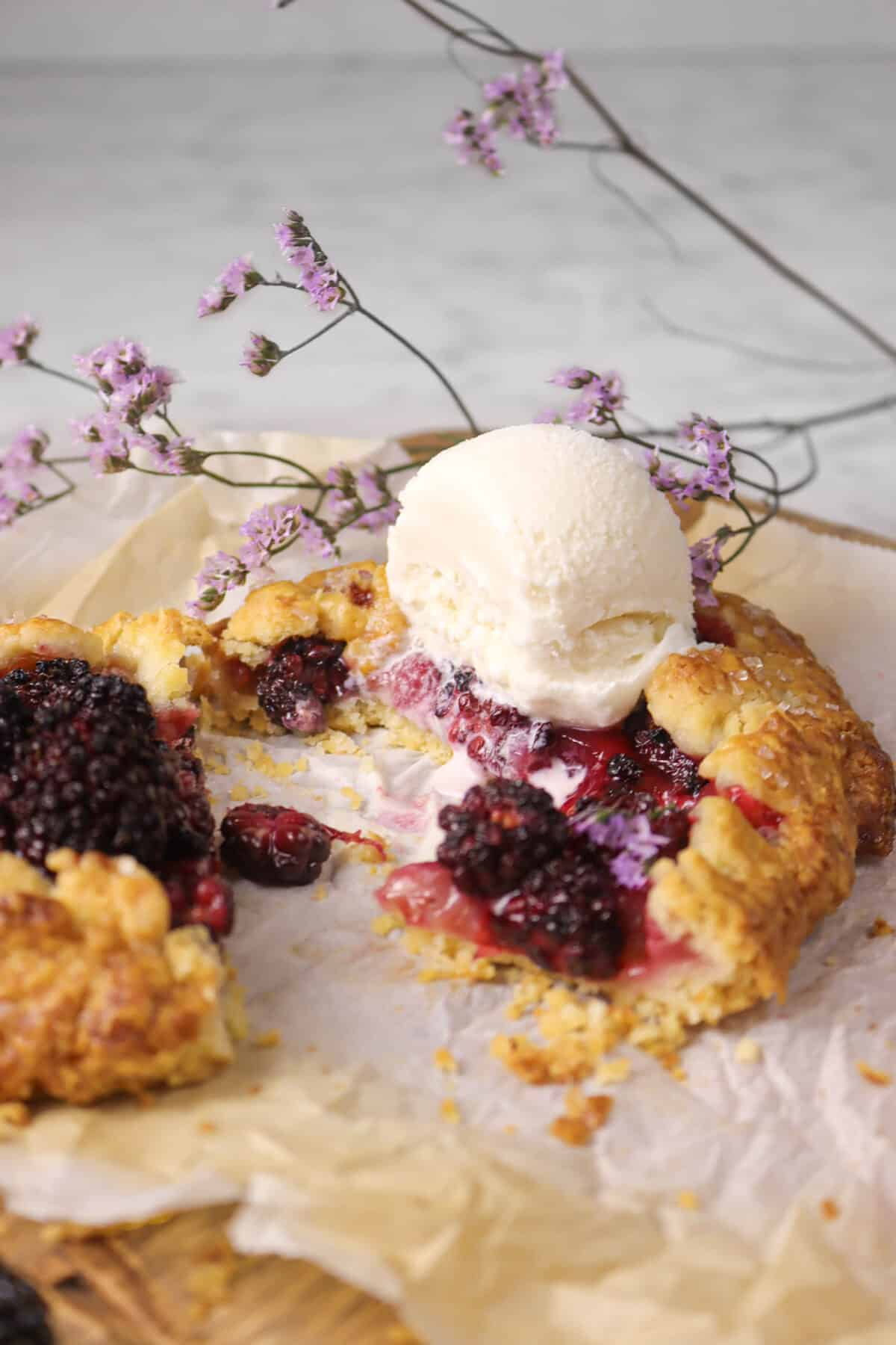 blackberry galette with a bite taken out of it with ice cream and flowers
