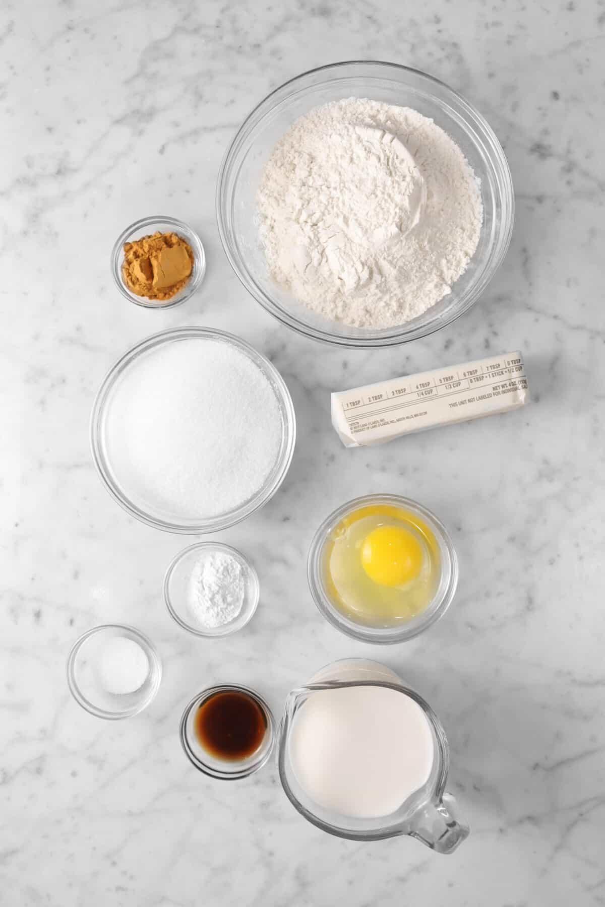 flour, cinnamon, sugar, salt, egg, baking powder, salt, vanilla, milk on marble counter