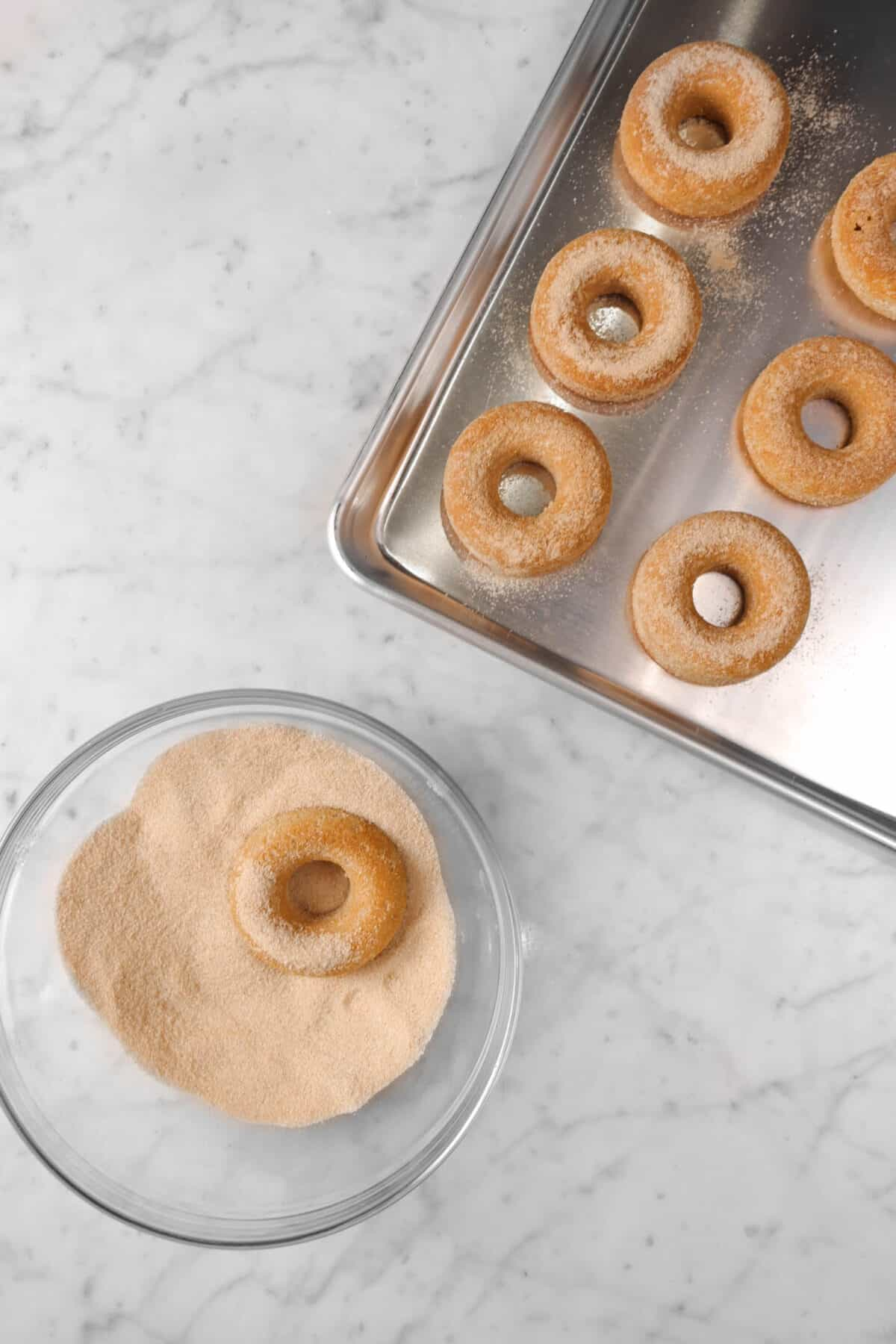 pan of cinnamon donuts with bowl of cinnamon sugar and a donut it