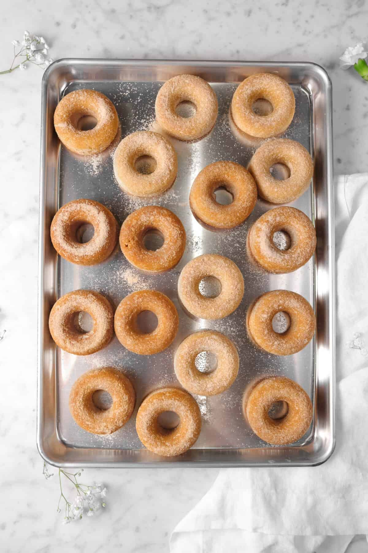 17 cinnamon donuts on a sheet pan with white napkin and flowers