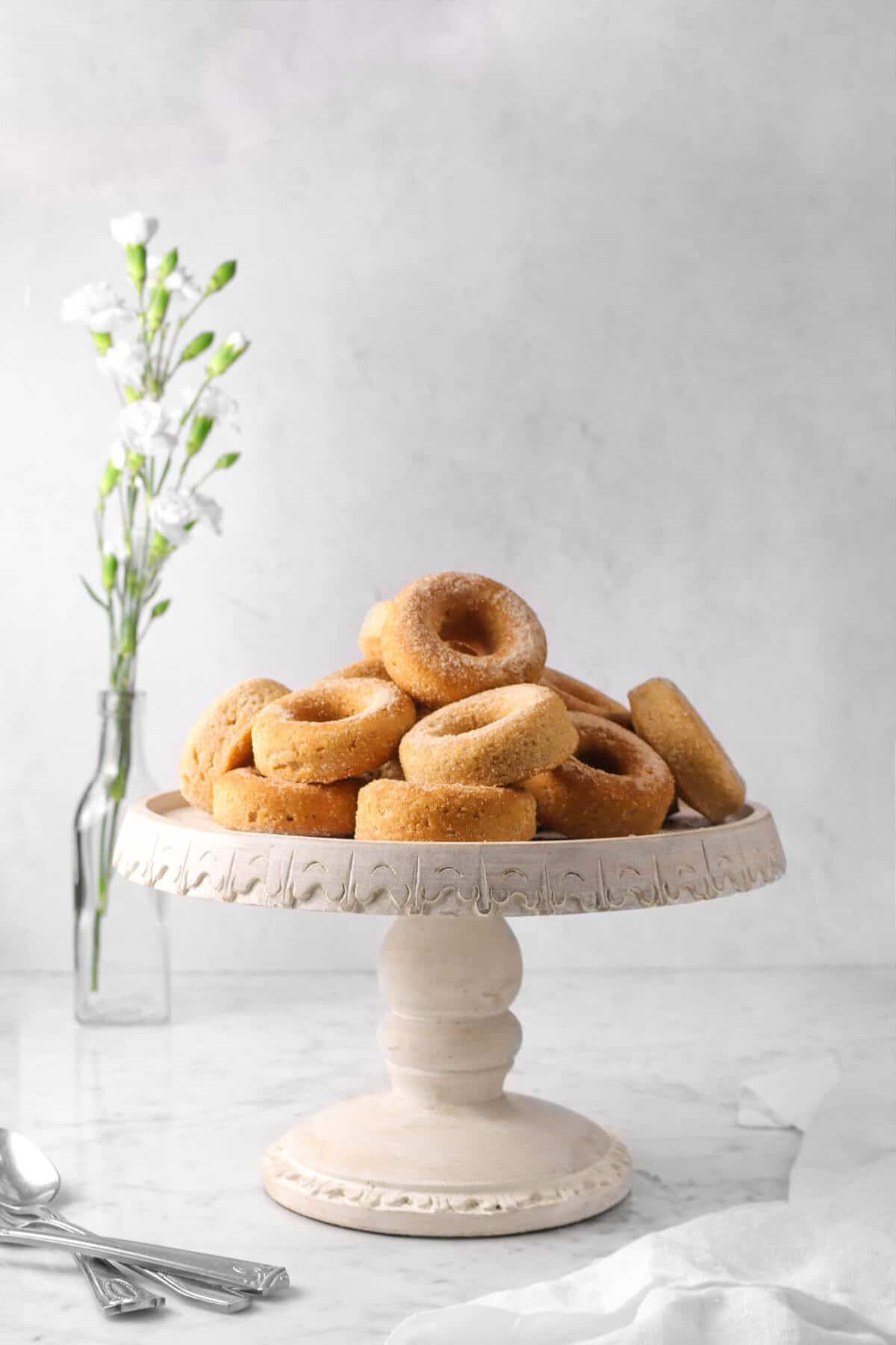 cinnamon donuts on a cake stand with flowers, white napkin, and silver utensils